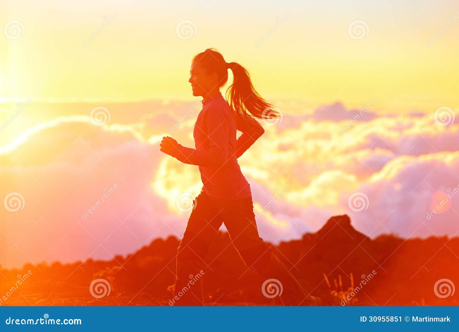 Corrida - corredor da mulher que movimenta-se no por do sol