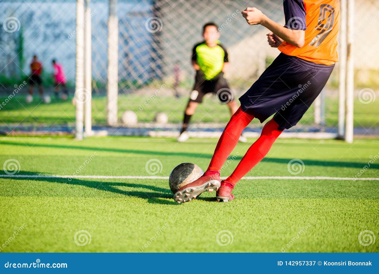 Corrida do jogador de futebol para disparar na bola no pontapé de grande penalidade ao objetivo com fundo obscuro do goleiros
