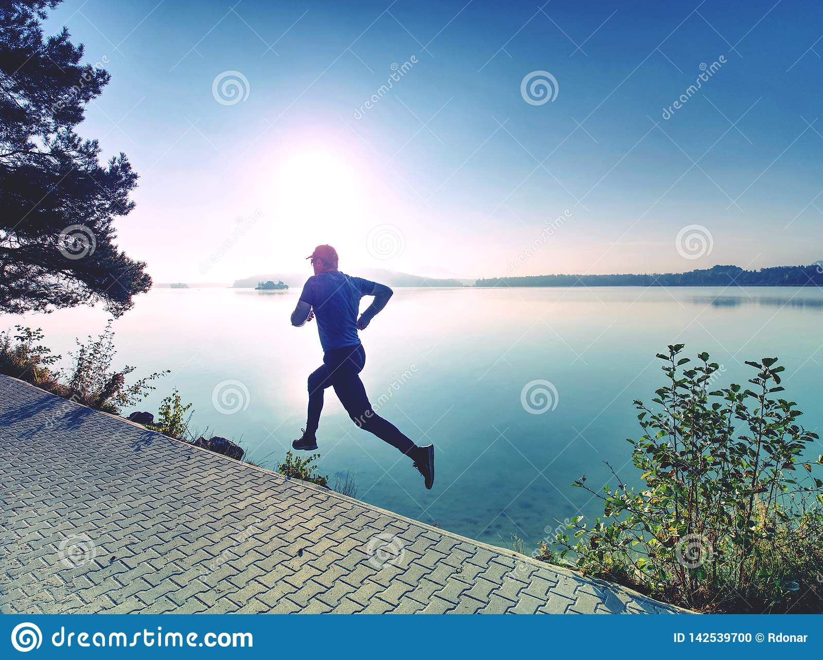 Corrida regular no lago Sprinting do corredor do homem exterior na natureza cénico