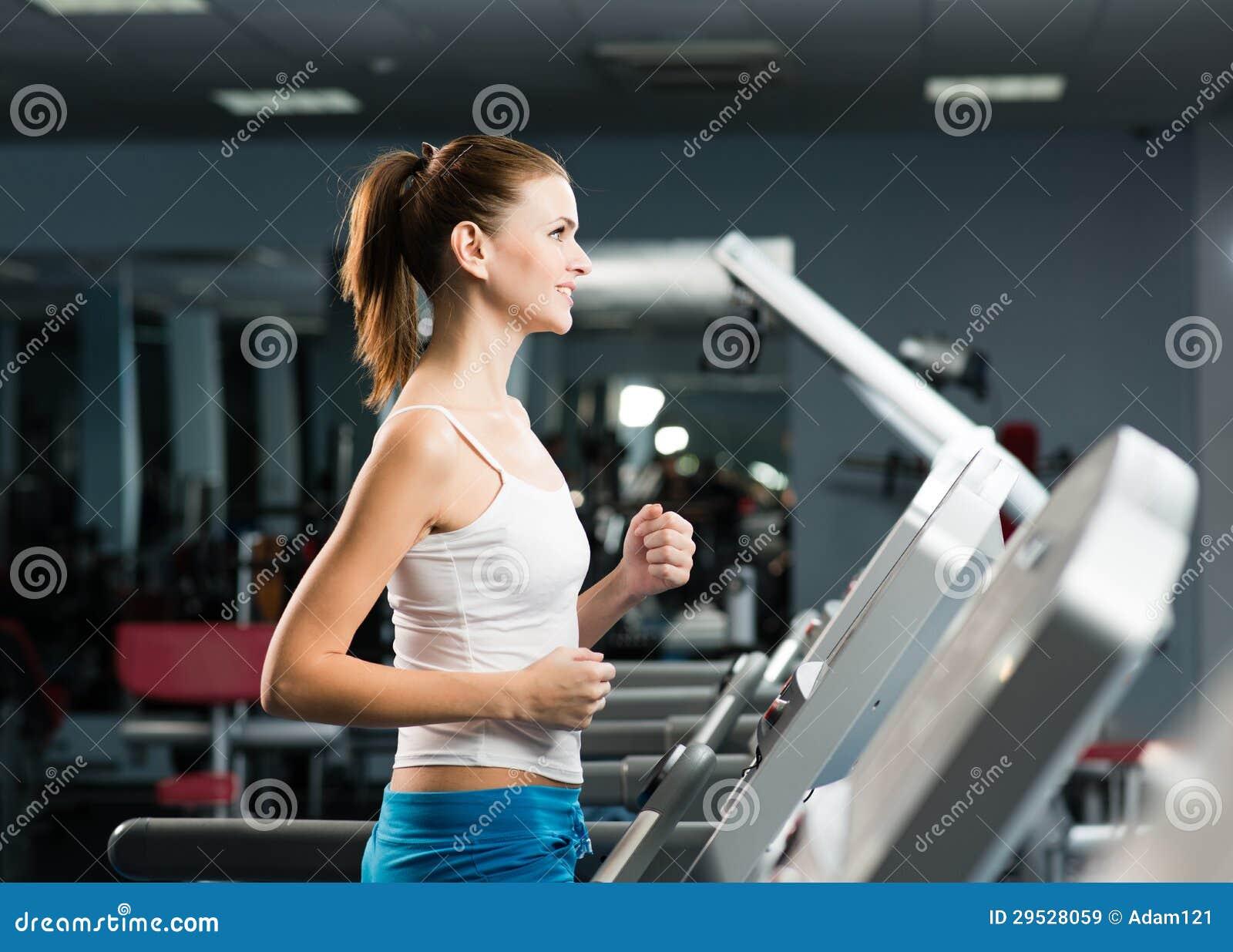 Corridas atrativas da jovem mulher em uma escada rolante