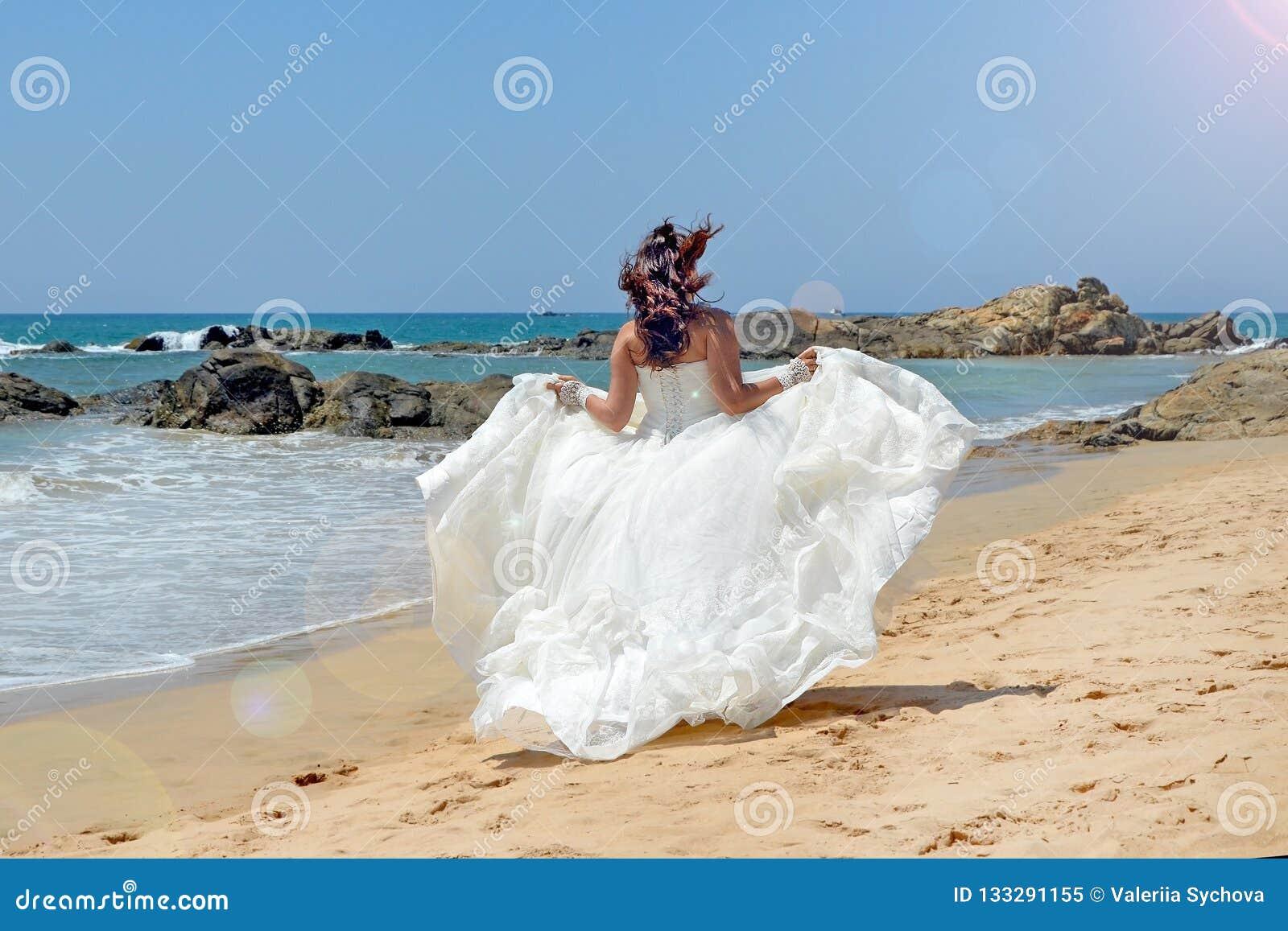 Corridas morenos de cabelos compridos da noiva ao longo do litoral arenoso no fundo das pedras no mar, a praia no Oceano Índico