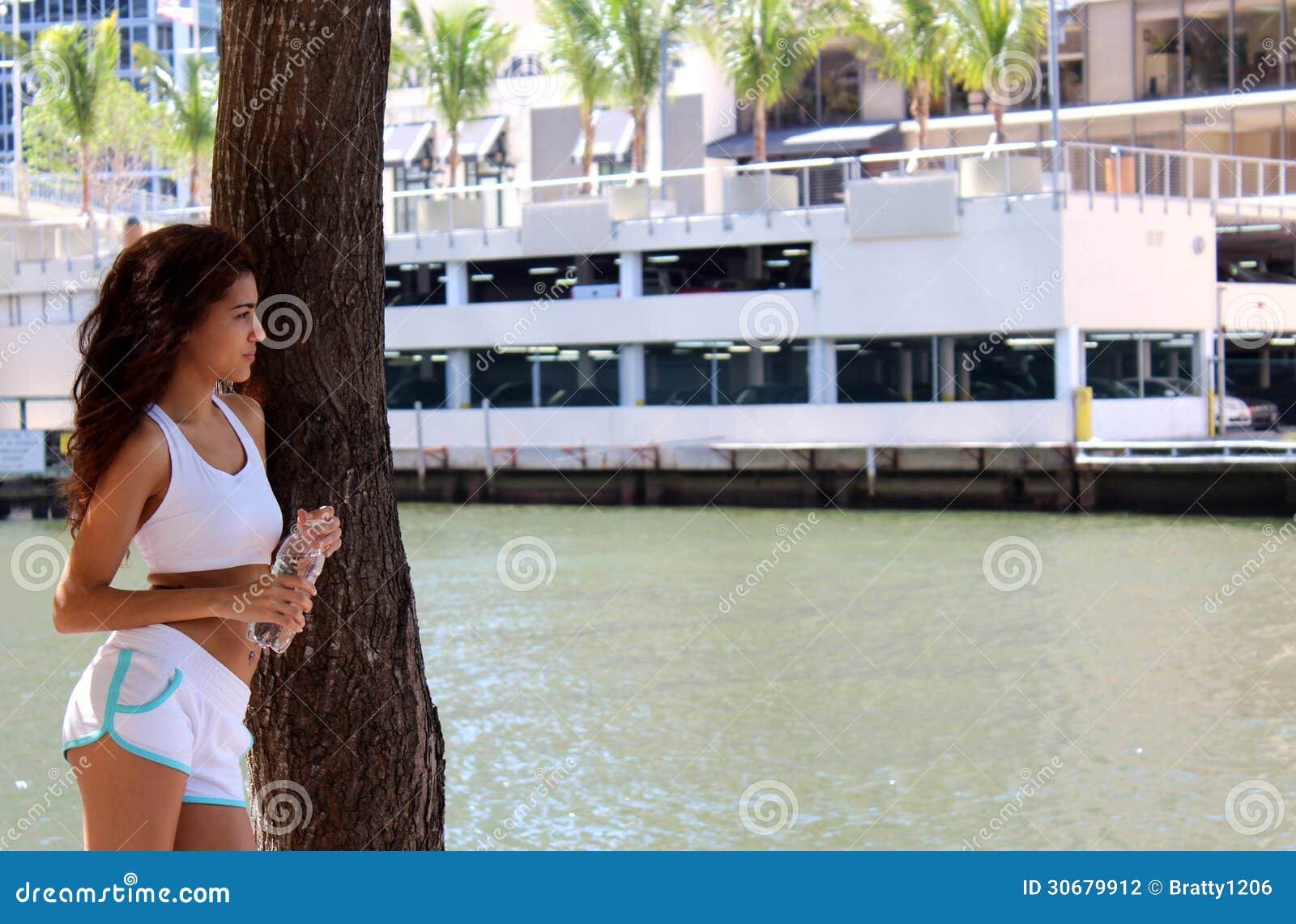 Corridore abbastanza giovane che prende una rottura vicino al bordo dell acqua