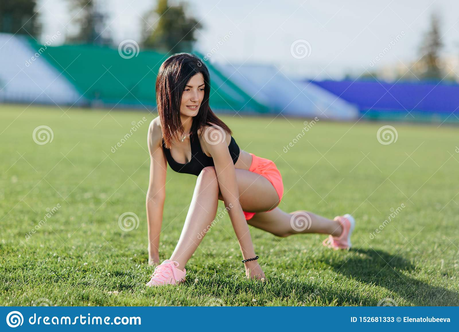 Corridore castana della donna sportiva nell usura di sport che fa le sessioni di allenamento sul campo in un vestito di sport di