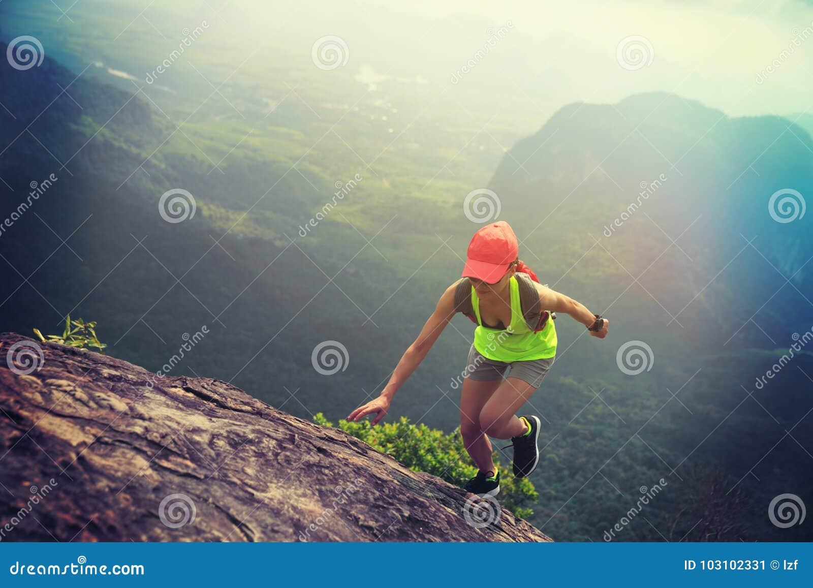 Corridore della traccia della donna di forma fisica che corre fino alla cima della montagna