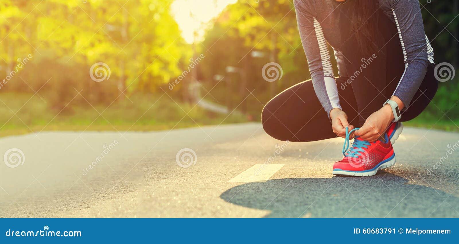 Corridore femminile che lega le sue scarpe che preparano per un trotto