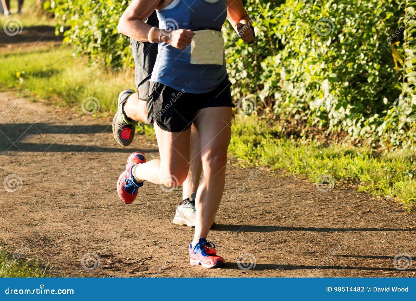 Corridori che corrono un 5K su un percorso della sporcizia