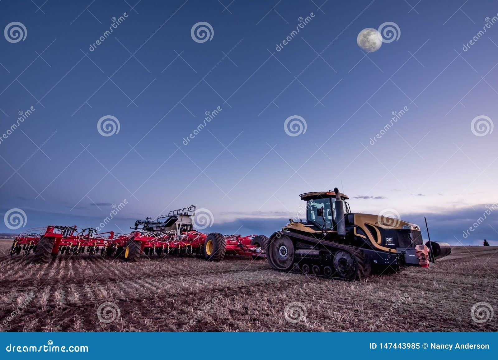 Corriente rápida, SK/Canada- 10 de mayo de 2019: La Luna Llena sobre el tractor de oruga y el aire de Bourgault perforan en el ca