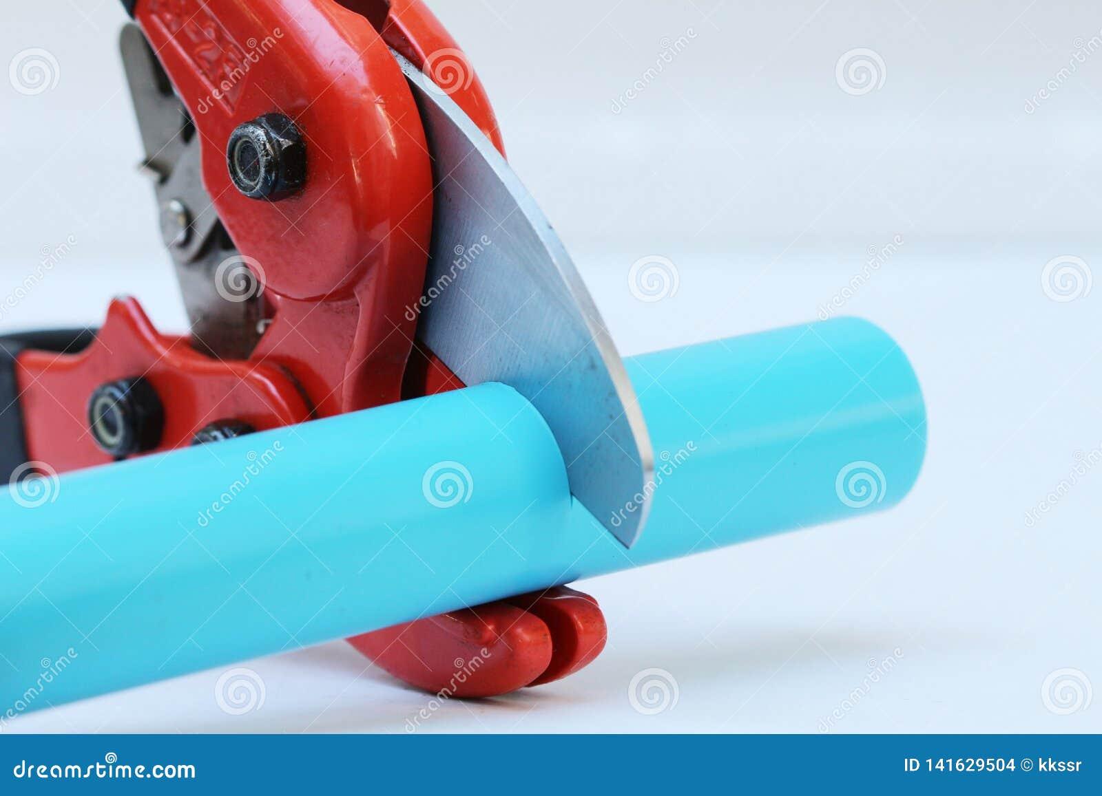 Cortador de tubo de agua del PVC con el cuerpo rojo del metal, la manija de goma negra y la cuchilla gruesa aguda en el fondo bla