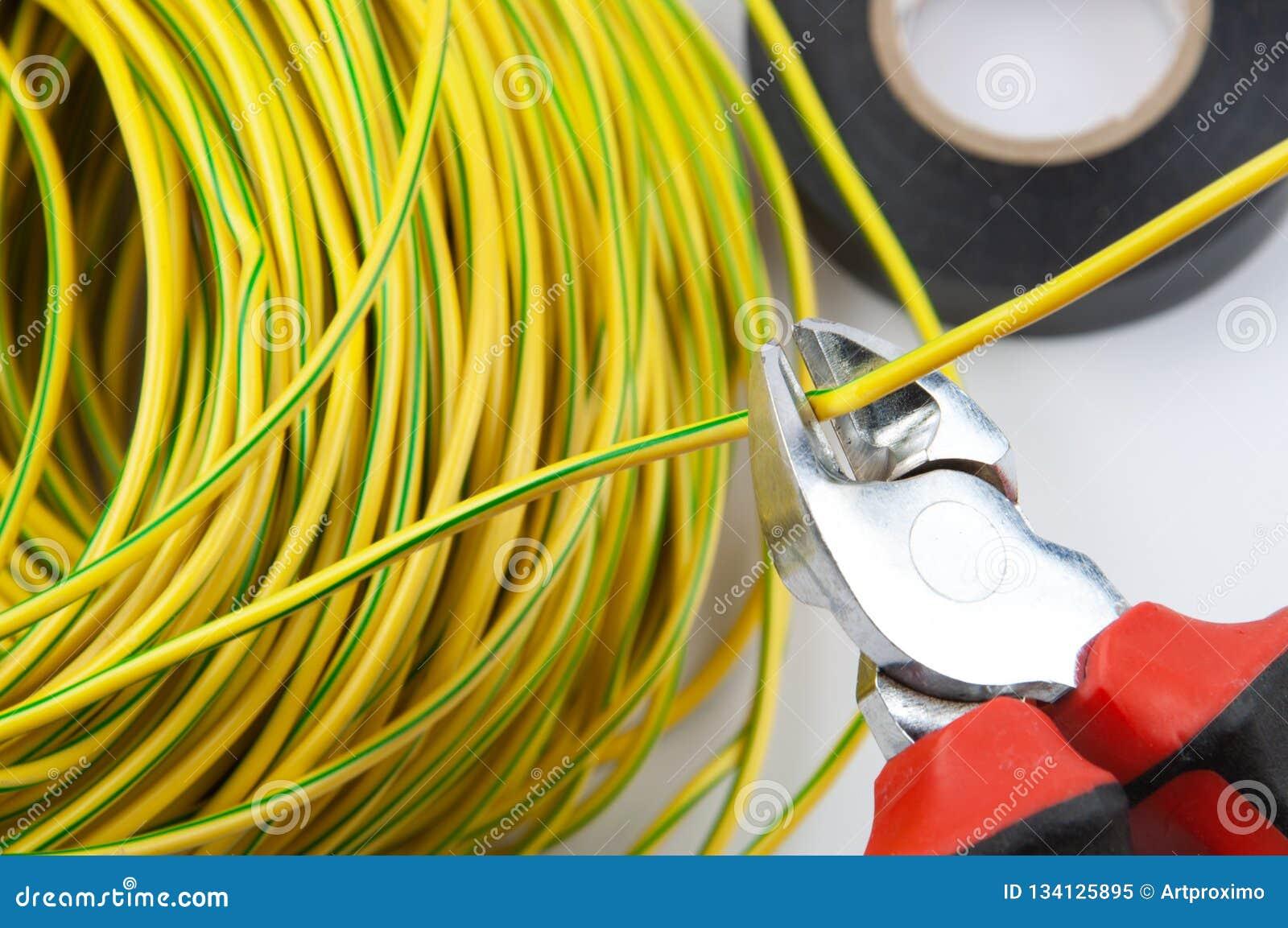 Cortadores de fio, com um pacote de fios verde-amarelos e de fita elétrica
