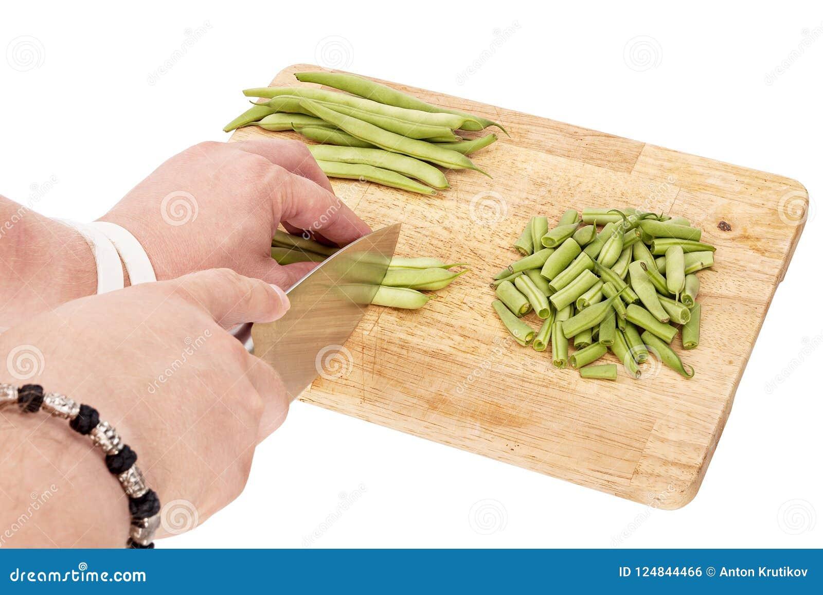 Cortar habas verdes frescas en una tabla de cortar en una tabla