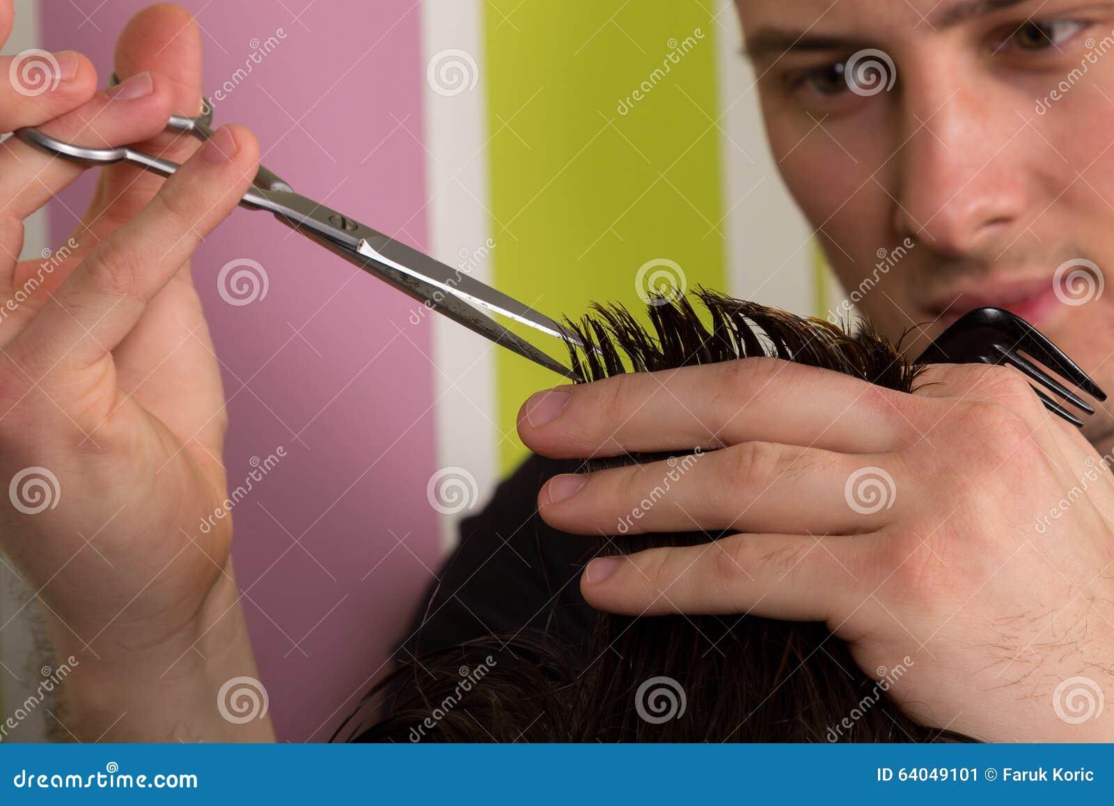 Corte del pelo de los hombres con las tijeras en un salón de belleza