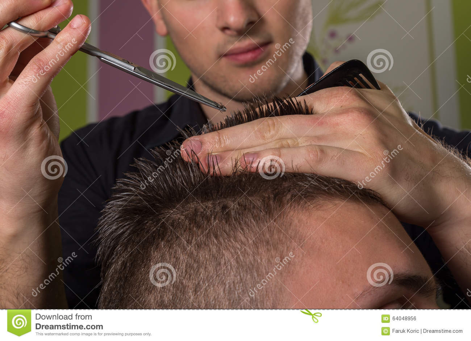 Corte do cabelo dos homens com tesouras em um salão de beleza