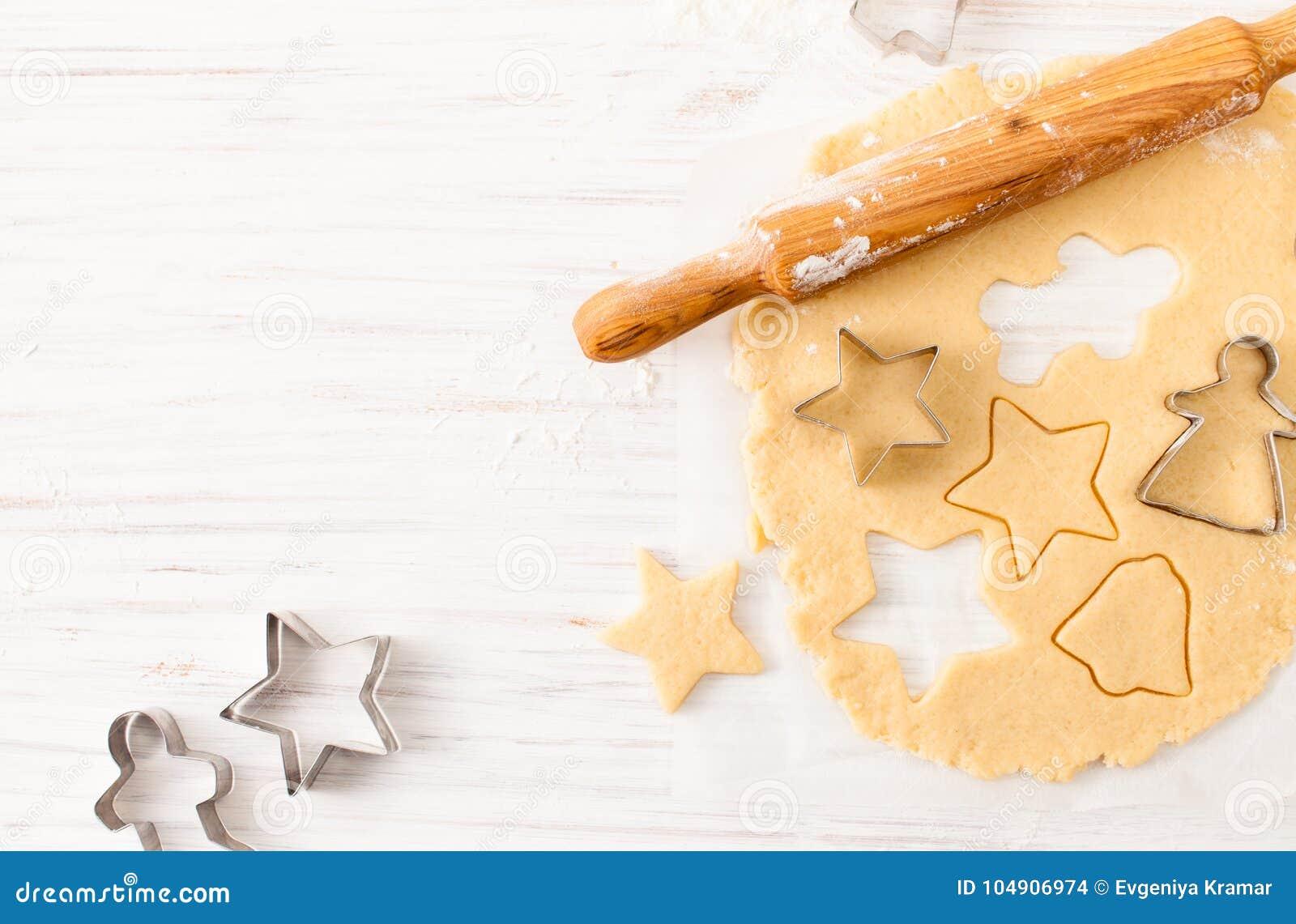 Corte a forma da cookie da massa na tabela branca Vista com espaço da cópia