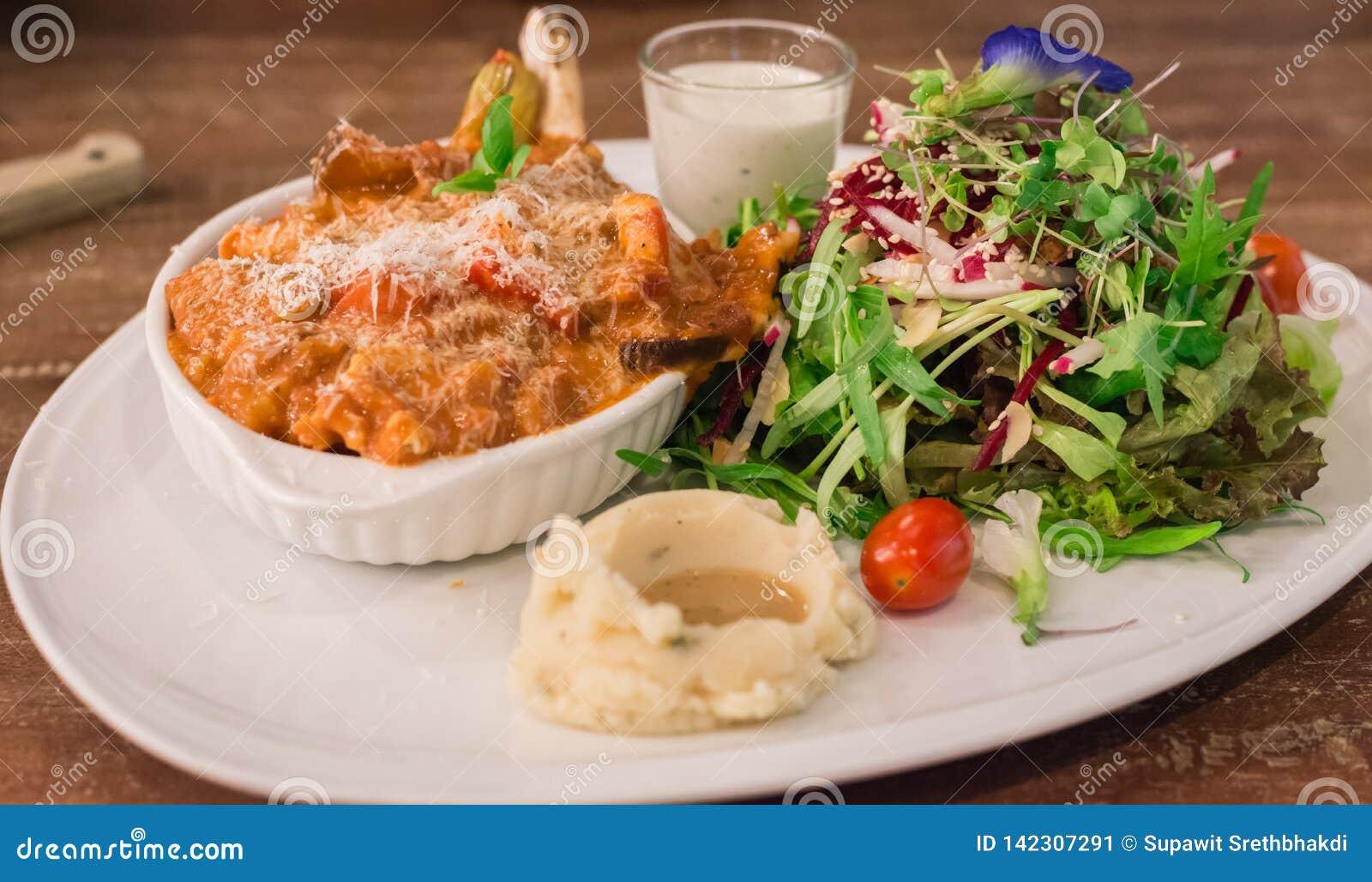Corte francés de la chuleta de cerdo con la salsa, la ensalada orgánica y el puré de patata con salsa