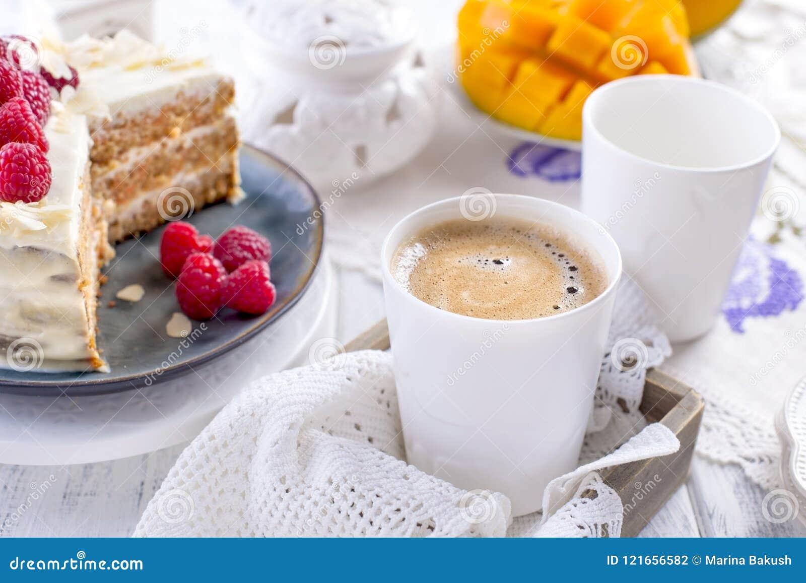 Corte o bolo com creme branco, para o fruto da manga do café da manhã A O fundo branco, toalha de mesa com laço, uma xícara de ca