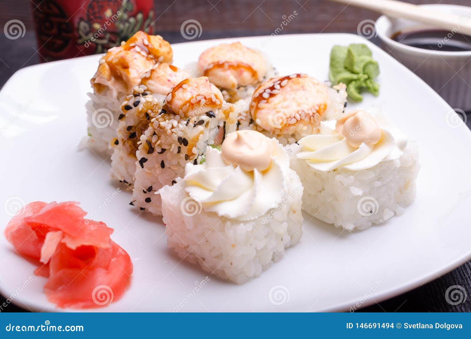Corte rolos de sushi em uma bandeja com gengibre e wasabi