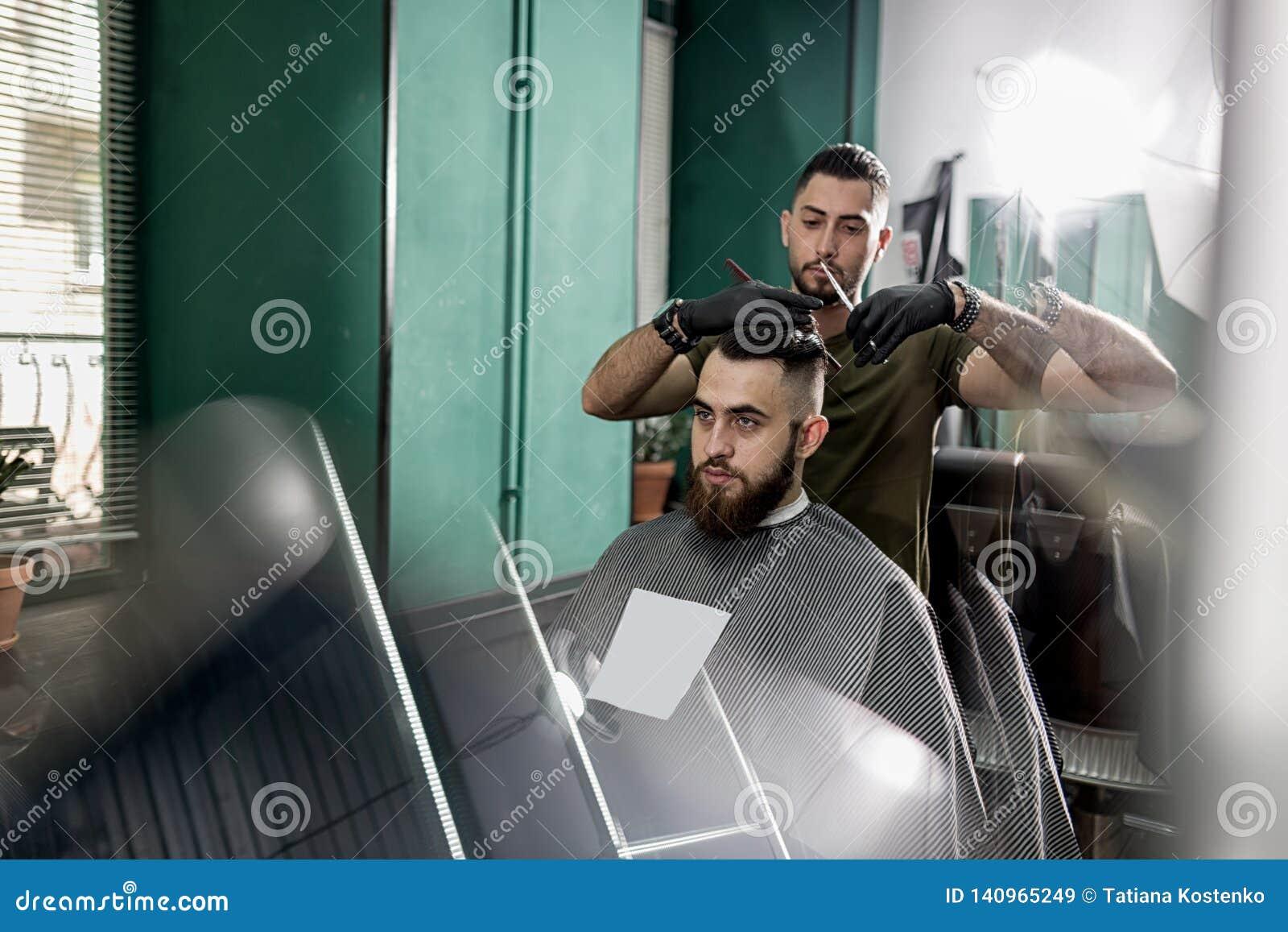 Cortes consideráveis do barbeiro com cabelo das tesouras do homem farpado à moda em um barbeiro