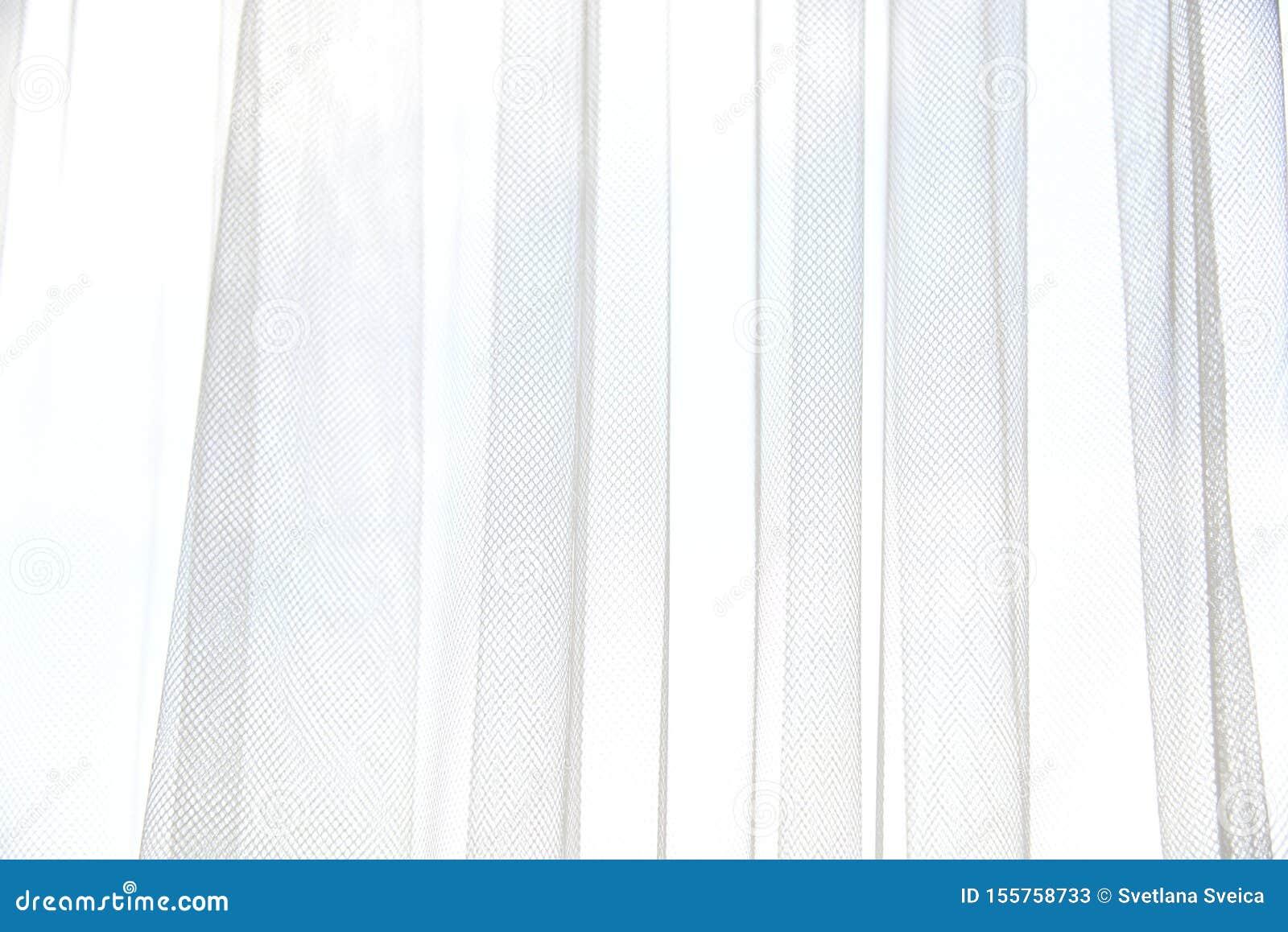 Cortina blanca de Tulle con los dobleces verticales Ventana con las cortinas ligeras Textura suave de la materia textil Extracto