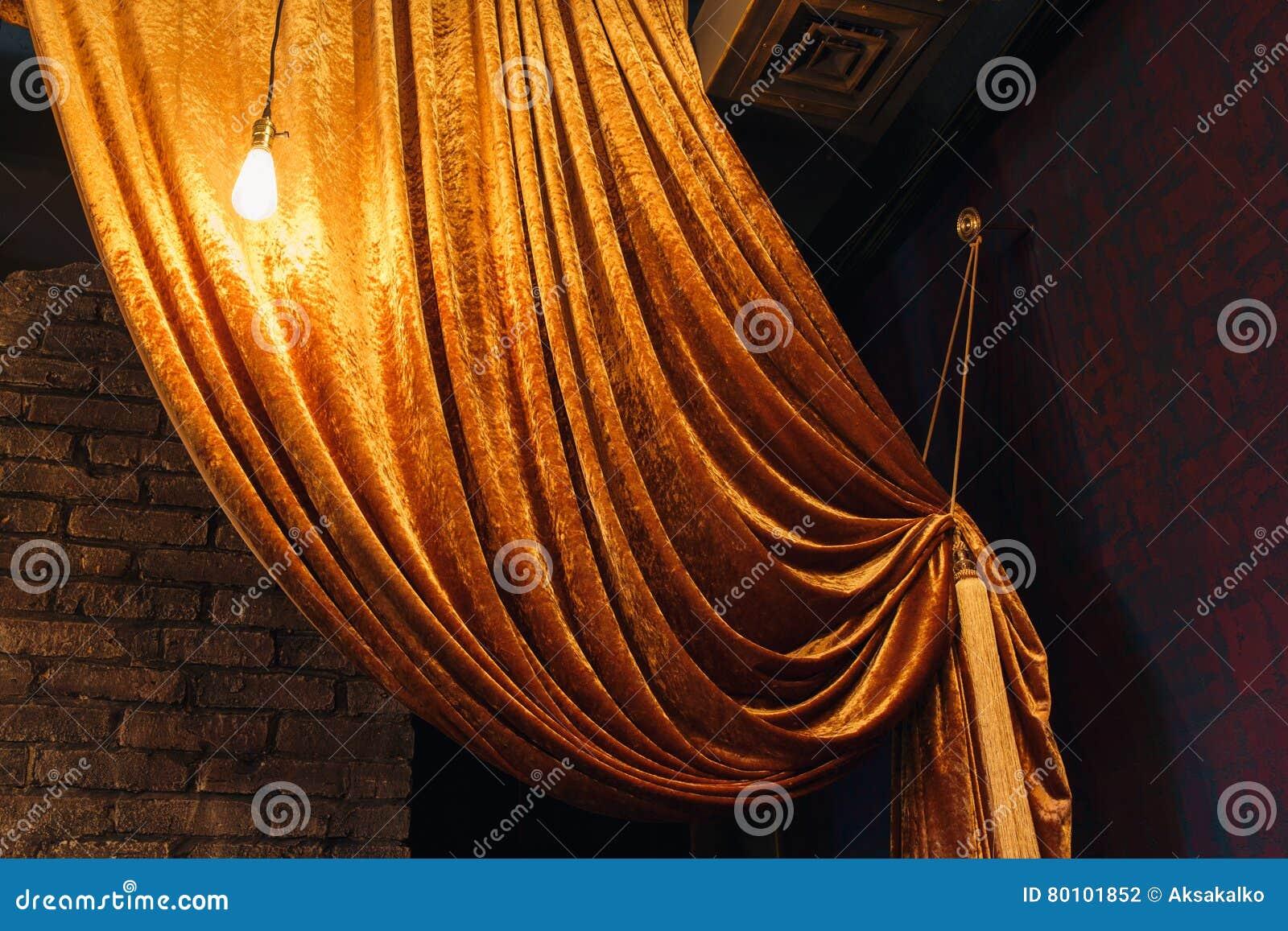 Cortina grande dourada na parede de tijolo