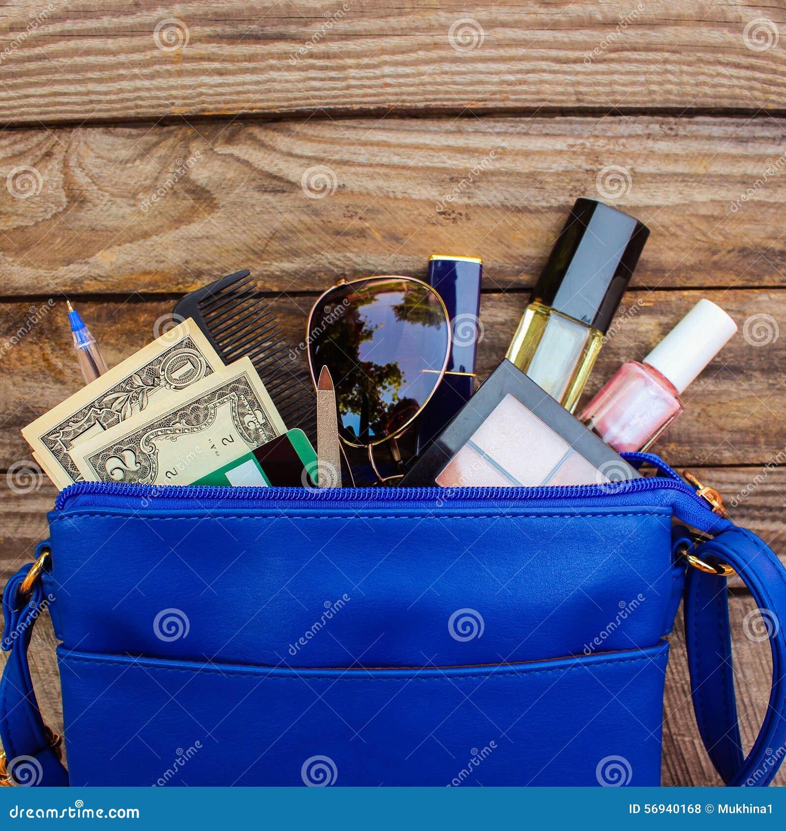Cosas del bolso abierto de la señora