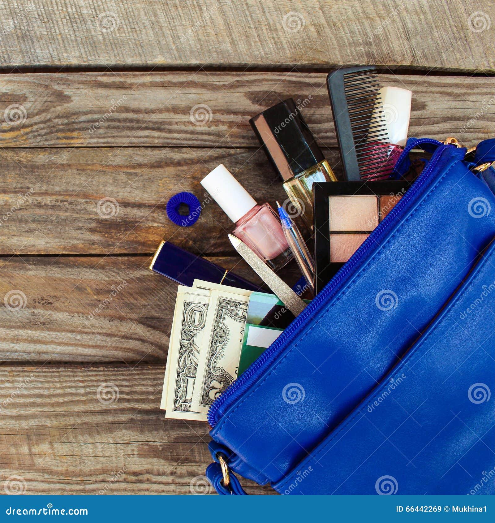 Cosas del bolso abierto de la señora el monedero de las mujeres en el fondo de madera