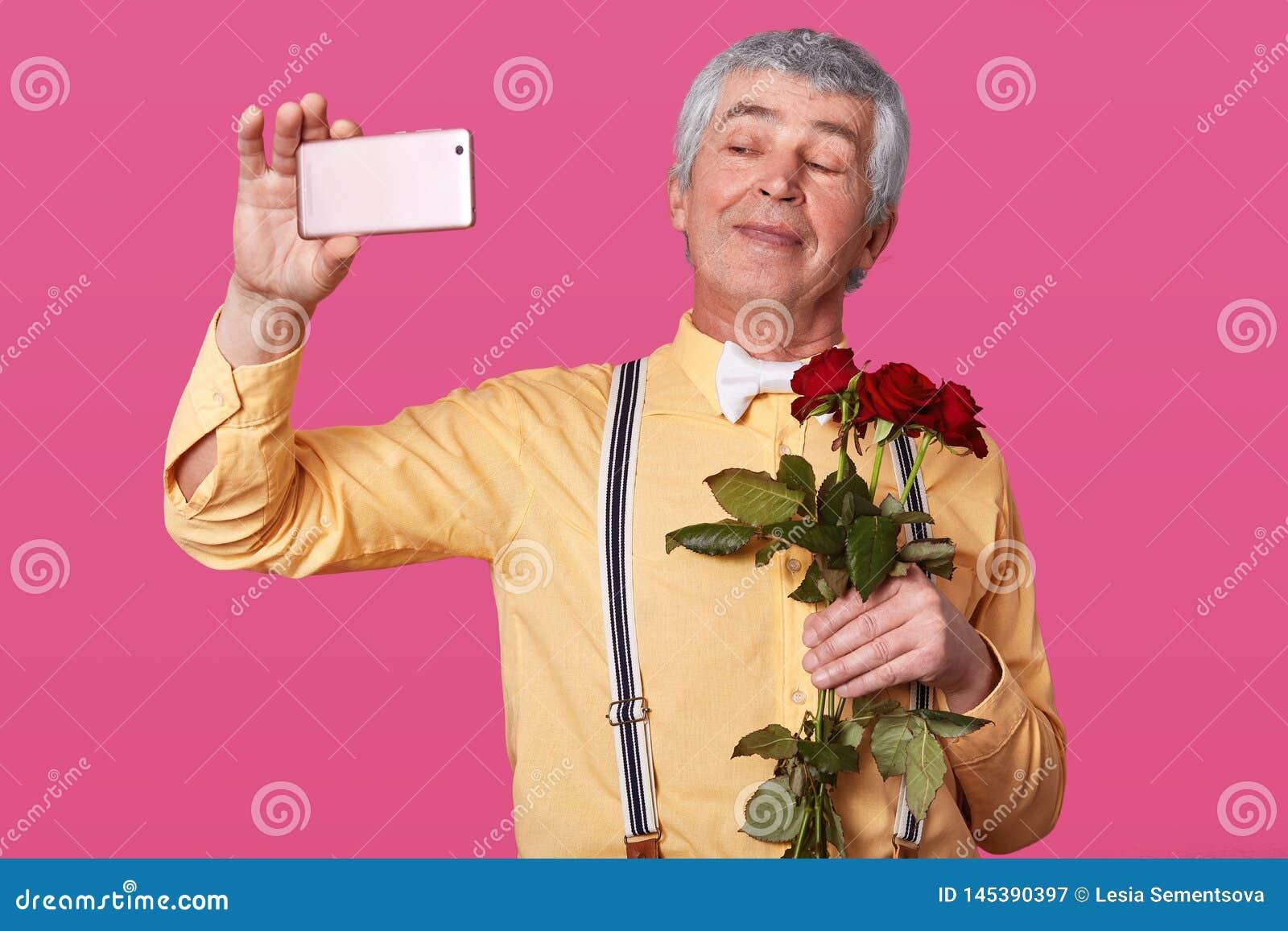 Cose w górę portreta przystojny starszy mężczyzna robi selfie jest ubranym żółtą koszula z suspenders przed datować, spo