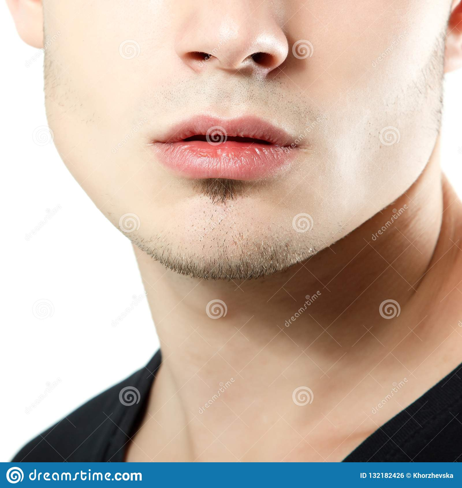 Coseup masculino de los labios, de la barbilla y del pómulo, detalle de la cara del hombre joven