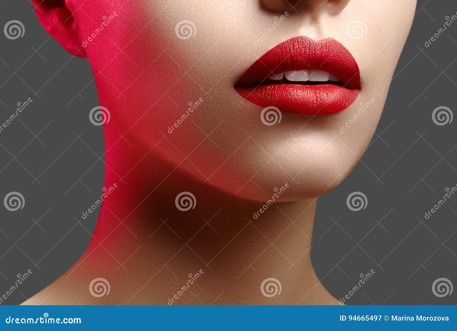 Cosméticos, maquillaje Lápiz labial brillante en los labios Primer de la boca femenina hermosa con maquillaje rojo del labio Limp