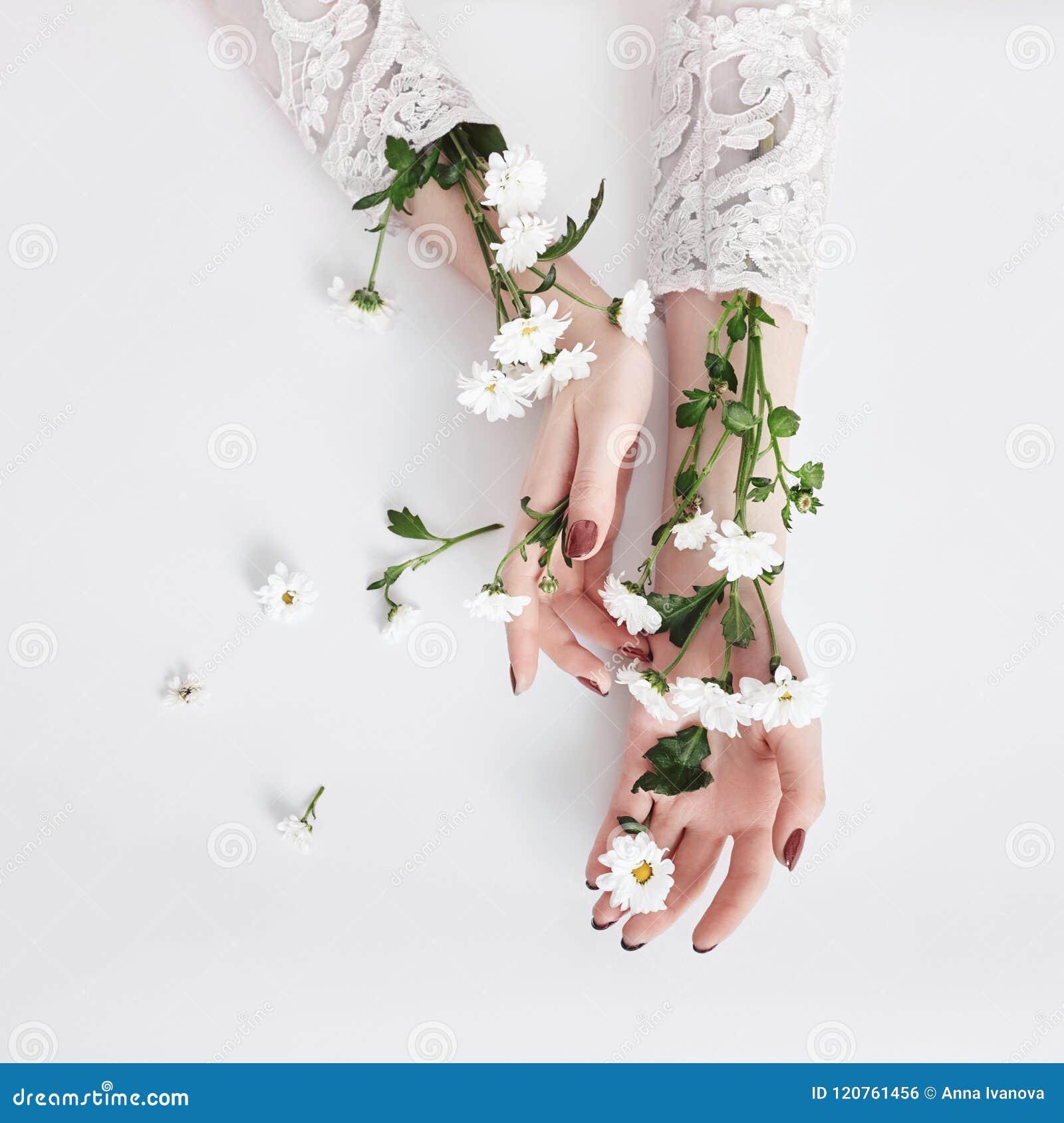 Cosméticos naturales de la mano de la belleza con el extracto de la flor, producto Mano en la tabla con la flor, cuidado de la mu