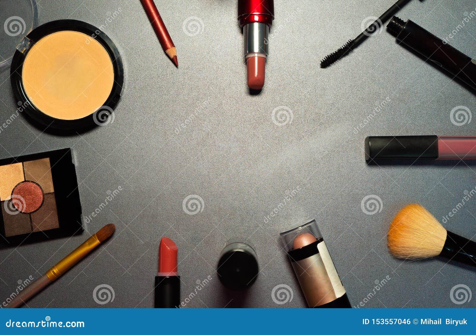 Cosméticos no fundo cinzento, close up, composição da mulher, ferramentas fêmeas