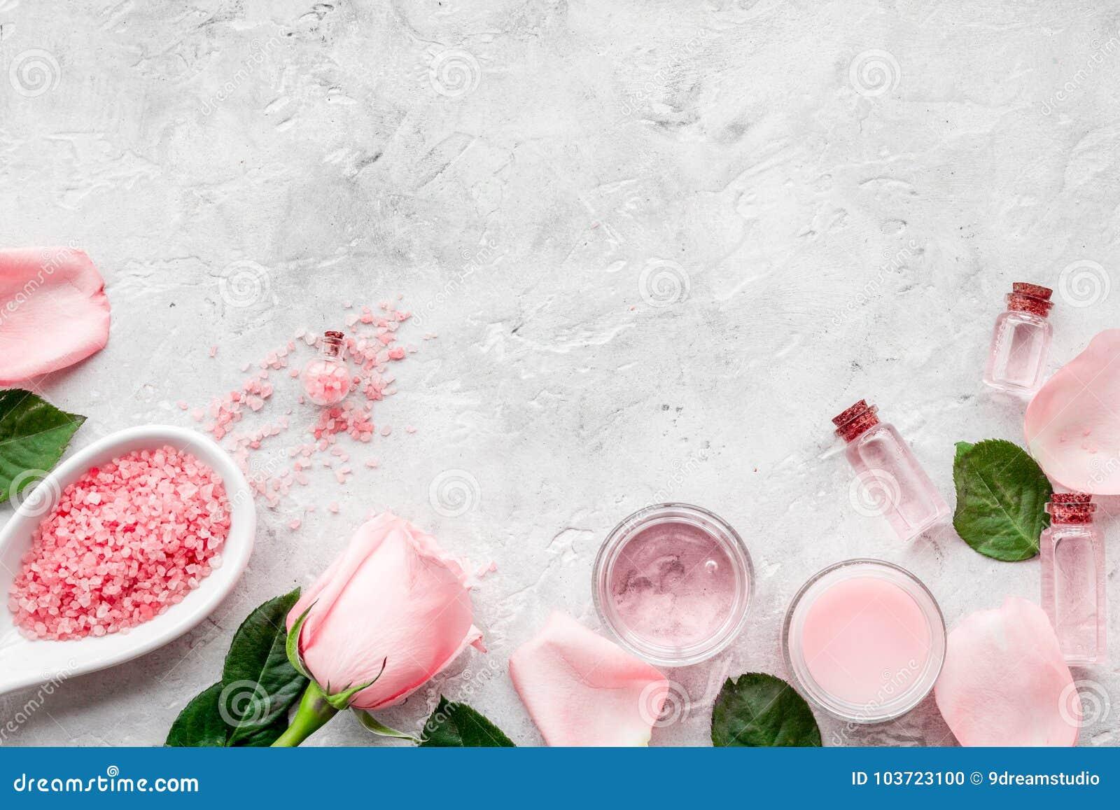 Cosméticos orgánicos naturales con aceite color de rosa Crema, loción, sal del balneario en copyspace gris de la opinión superior