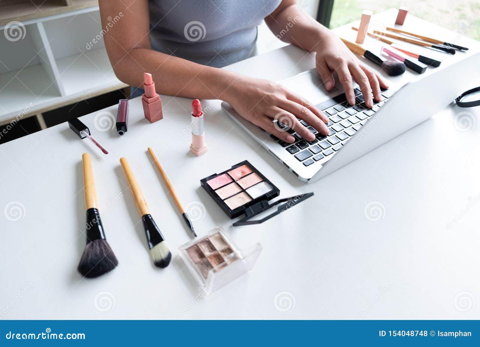 Cosmétiques actuels de beauté de blogger de beauté se reposant dans le comprimé avant Le bel examen de cosmétiques d utilisation