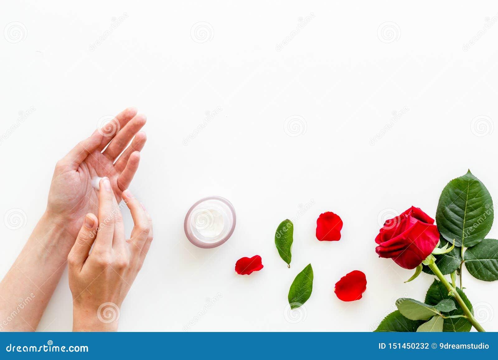 Cosmétiques organiques naturels avec l extrait rose dans des mains sur le copyspace blanc de vue supérieure de fond