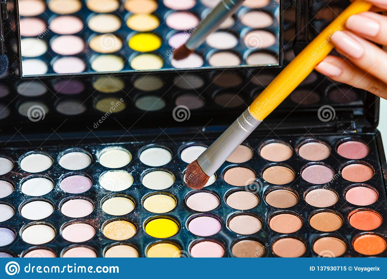 Woman holds makeup eye shadows palette and brush