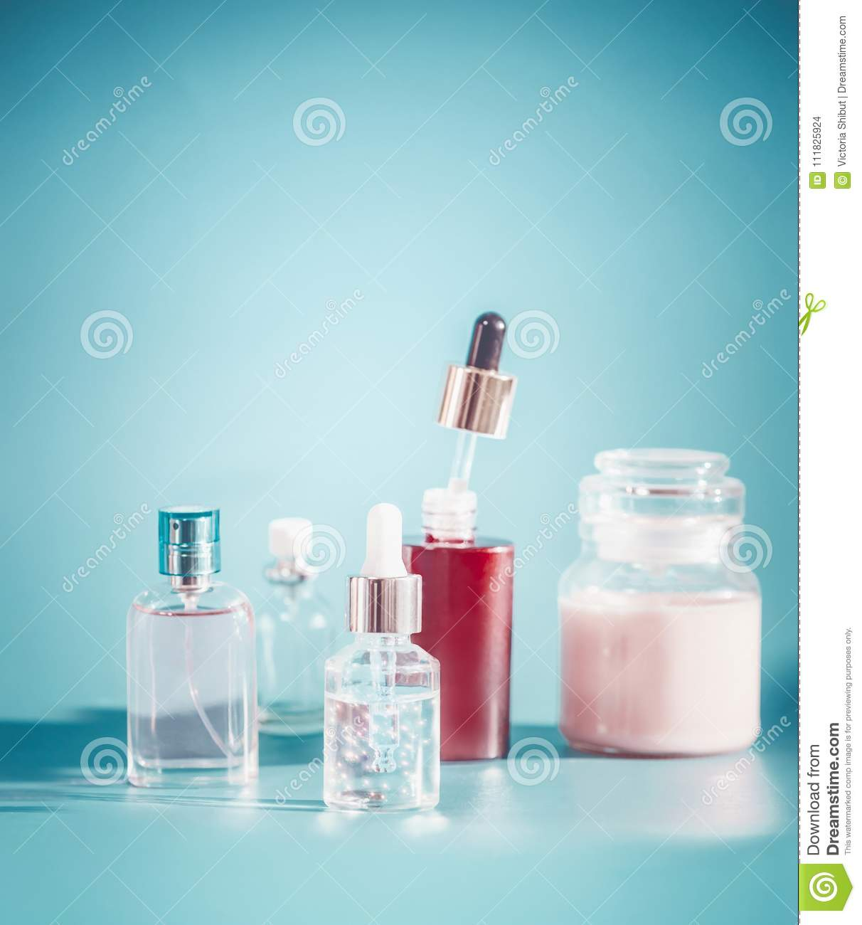 Cosmetic in bottle containers. Skin care setting with toner, essence,serum and cream on turquoise blue background , front view. Be