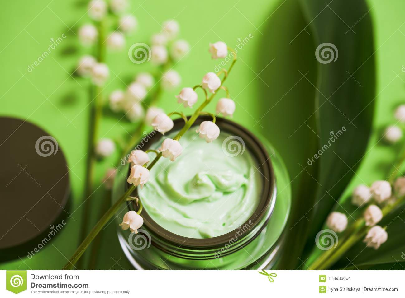 cosmetic cream and lily of the valley flowers on a green background.