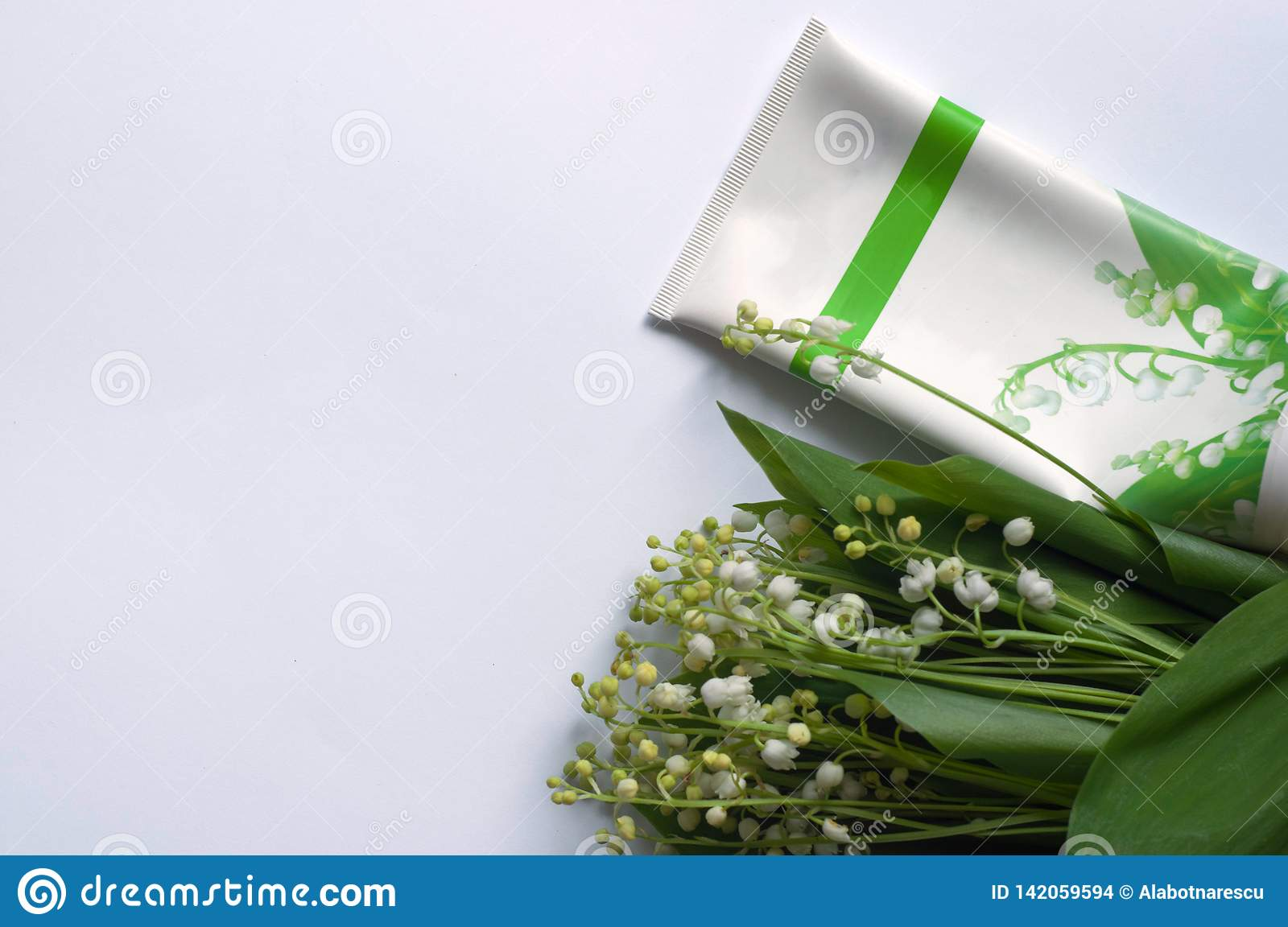 Cosmetic cream and lily of the valley flowers  on white background