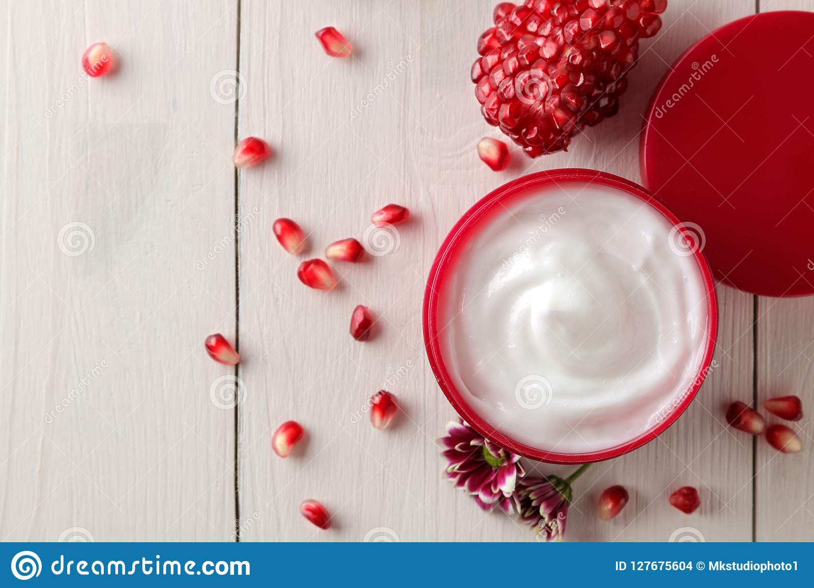 Cosmetic cream in a red jar with flowers and fresh pomegranate on a white wooden table. pomegranate extract. cosmetics.