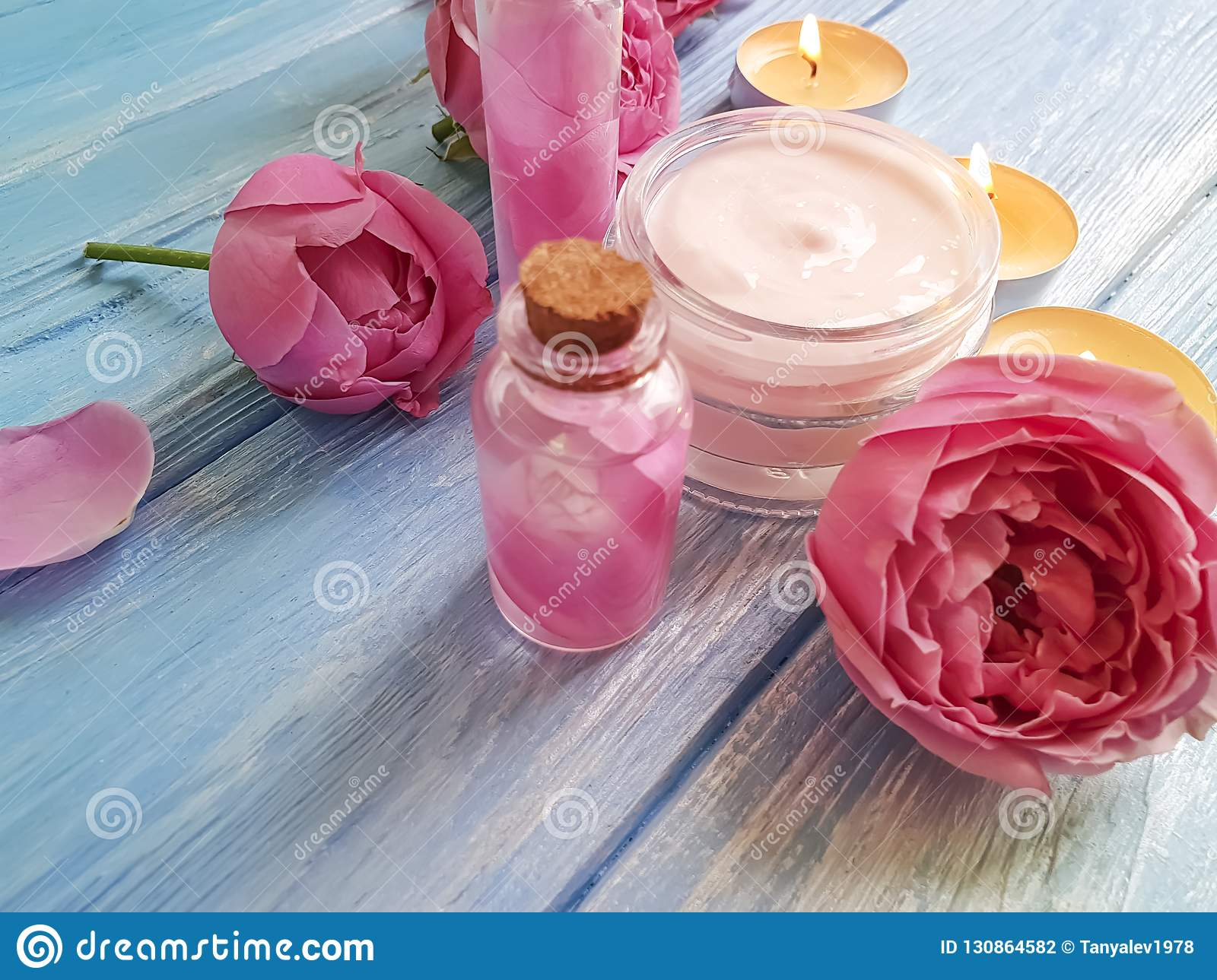 cosmetic cream , rose natural composition beautiful essence, candle on wooden background