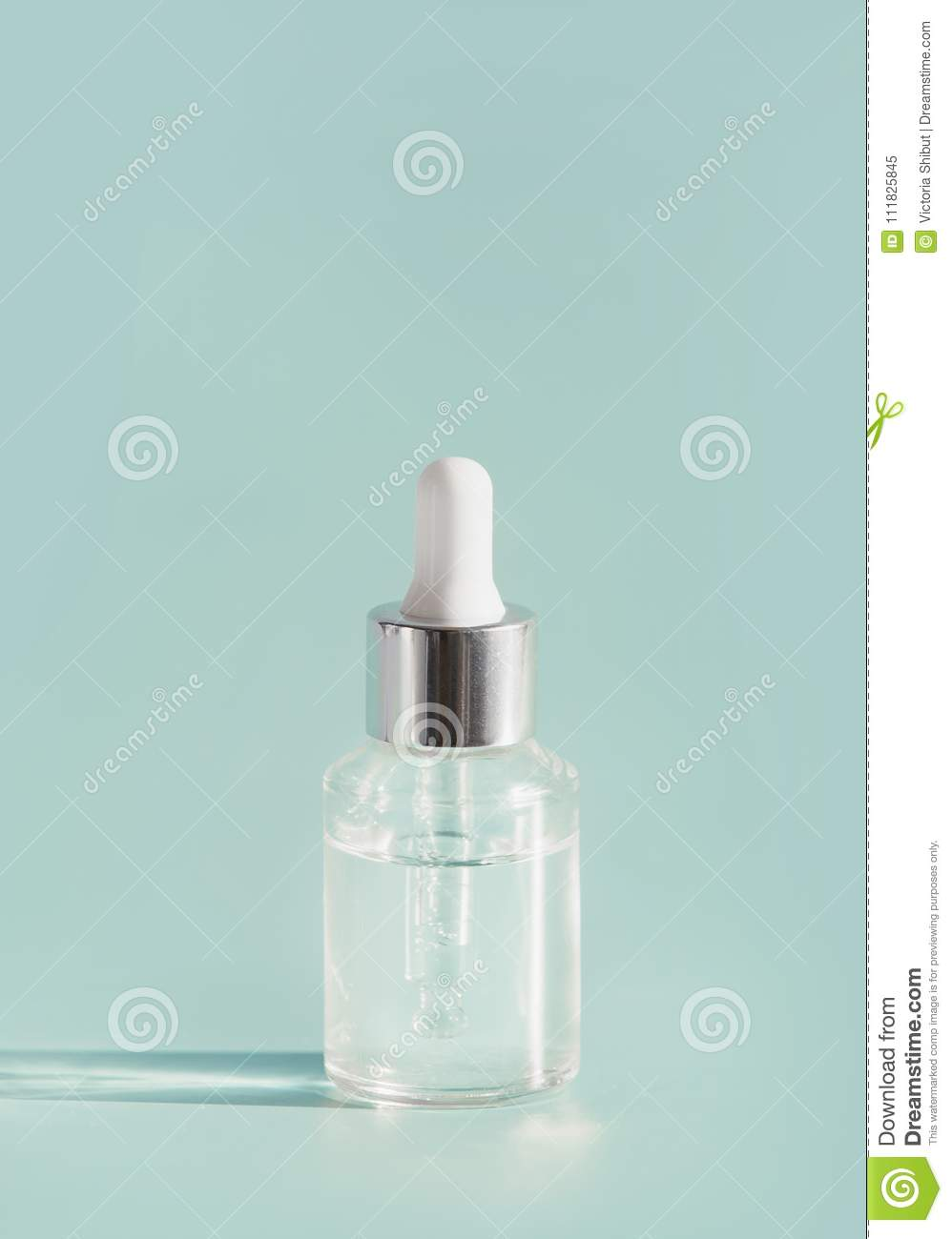 Cosmetic transparent liquid in glass bottle with dropper. Serum skin care product on light mint background, front view with copy s