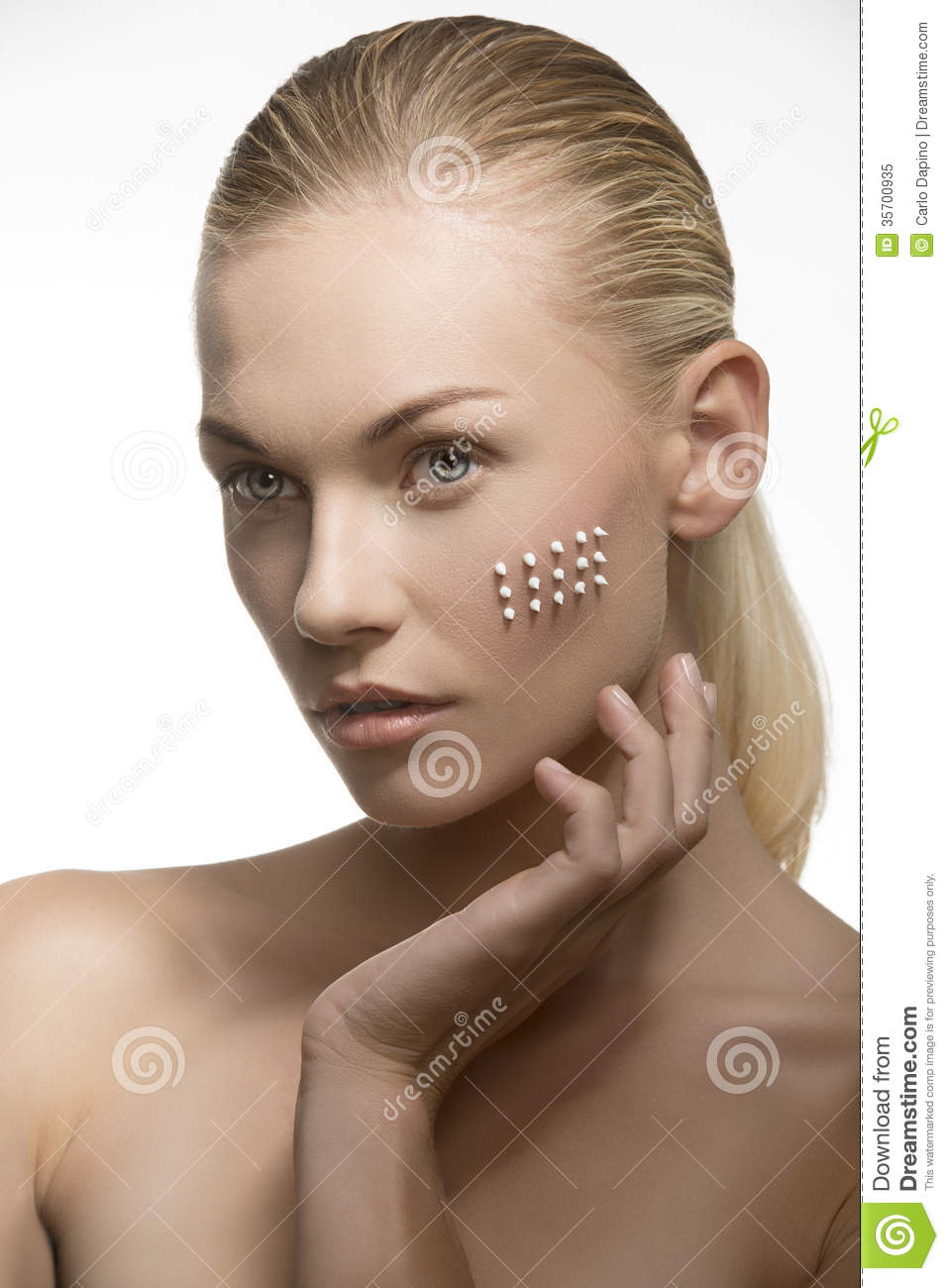 ... hair and naked shoulder applying cosmetic cream on her perfect visage