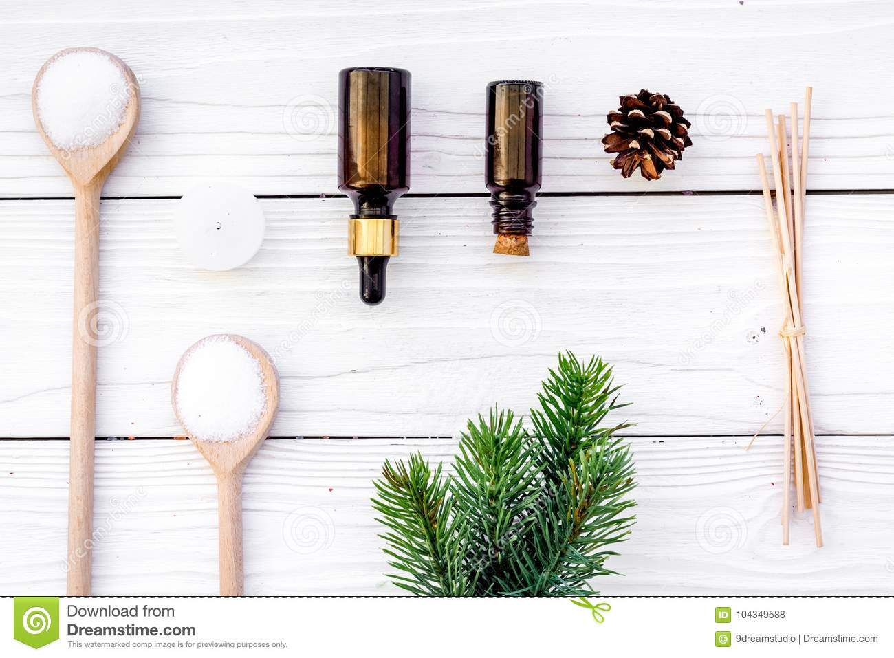 Cosmetics and aromatherapy concept. Pine spa salt, oil, pinecones and spruce branch on white wooden background top view