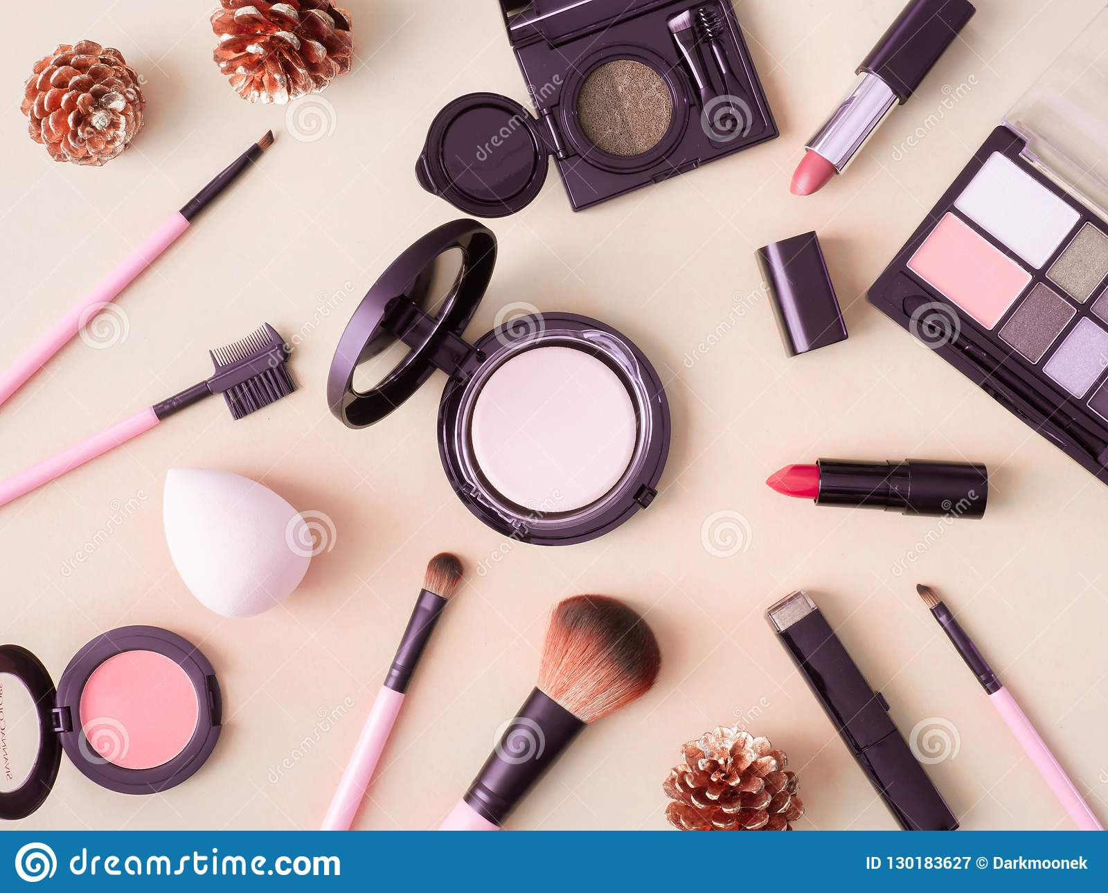 Cosmetics concept with lipstick, makeup products, Eyeshadow Palette, powder on cream color table background.