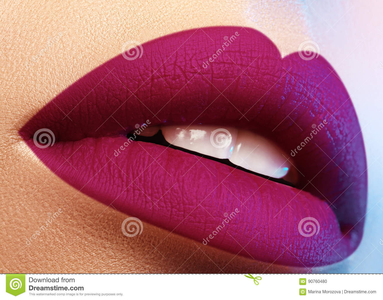 Cosmetics, makeup. Bright lipstick on lips. Closeup of beautiful female mouth with purple lip makeup. Part of face