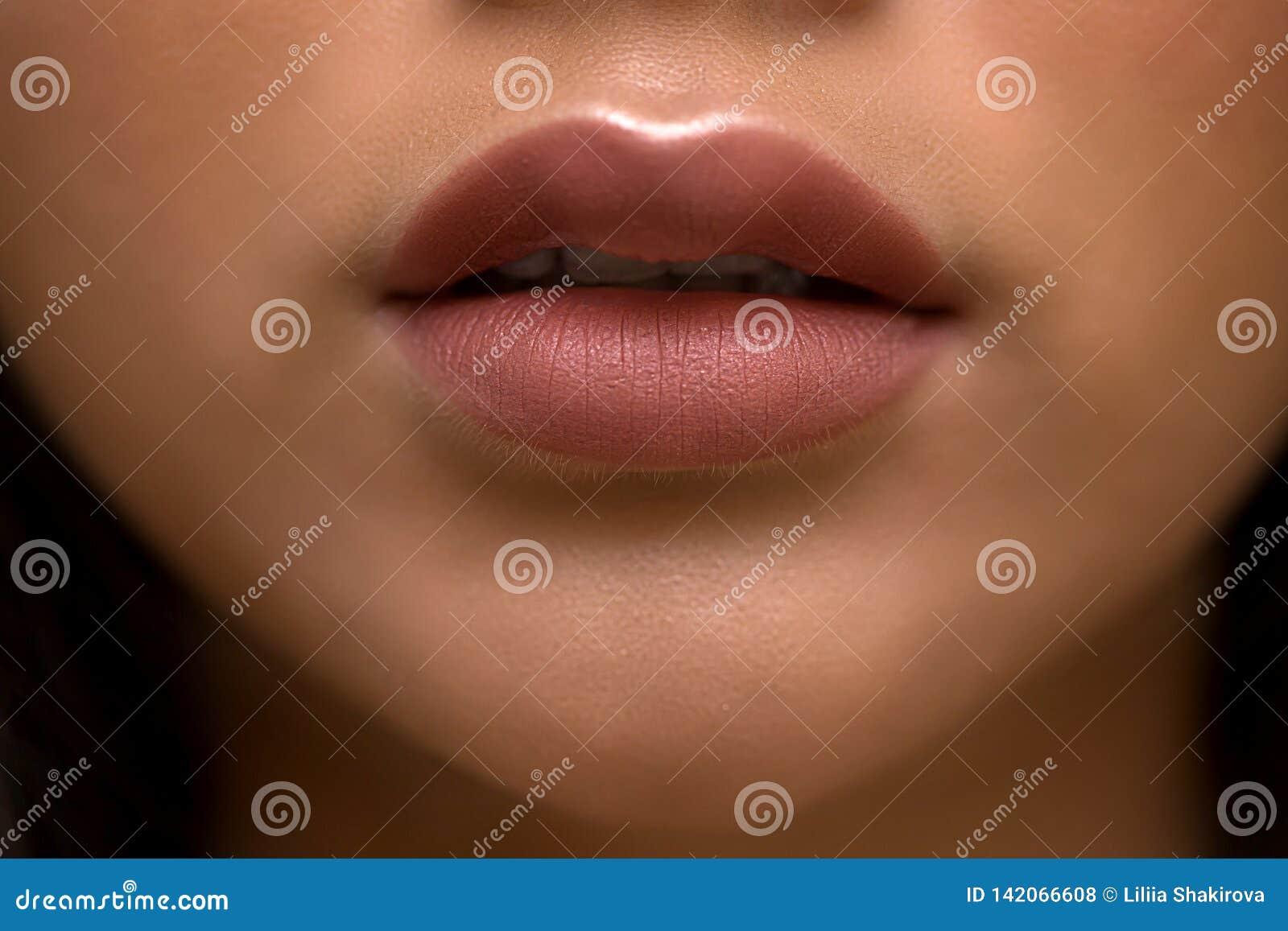 Cosmetics, makeup, is lipstick, a Nude shade, light brown gloss, close-up, half open lips, clean skin girls