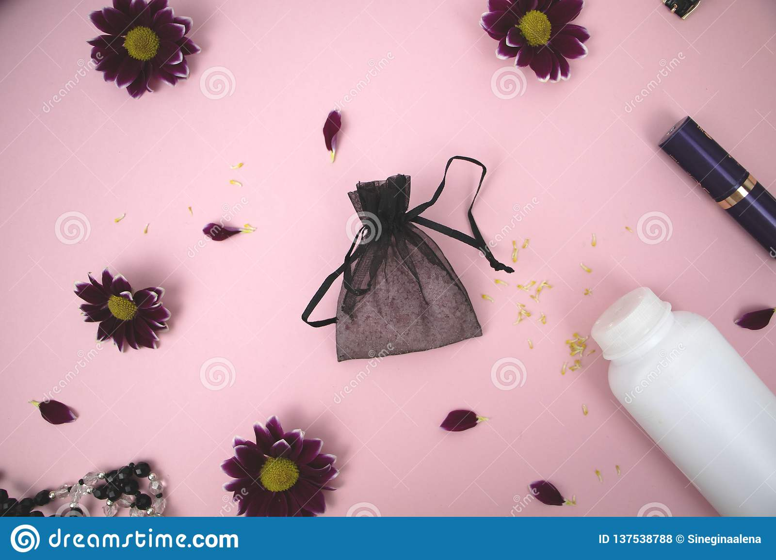 Cosmetics on the table at the woman. Cosmetic bag, cosmetic and hygiene products. Pink background for text