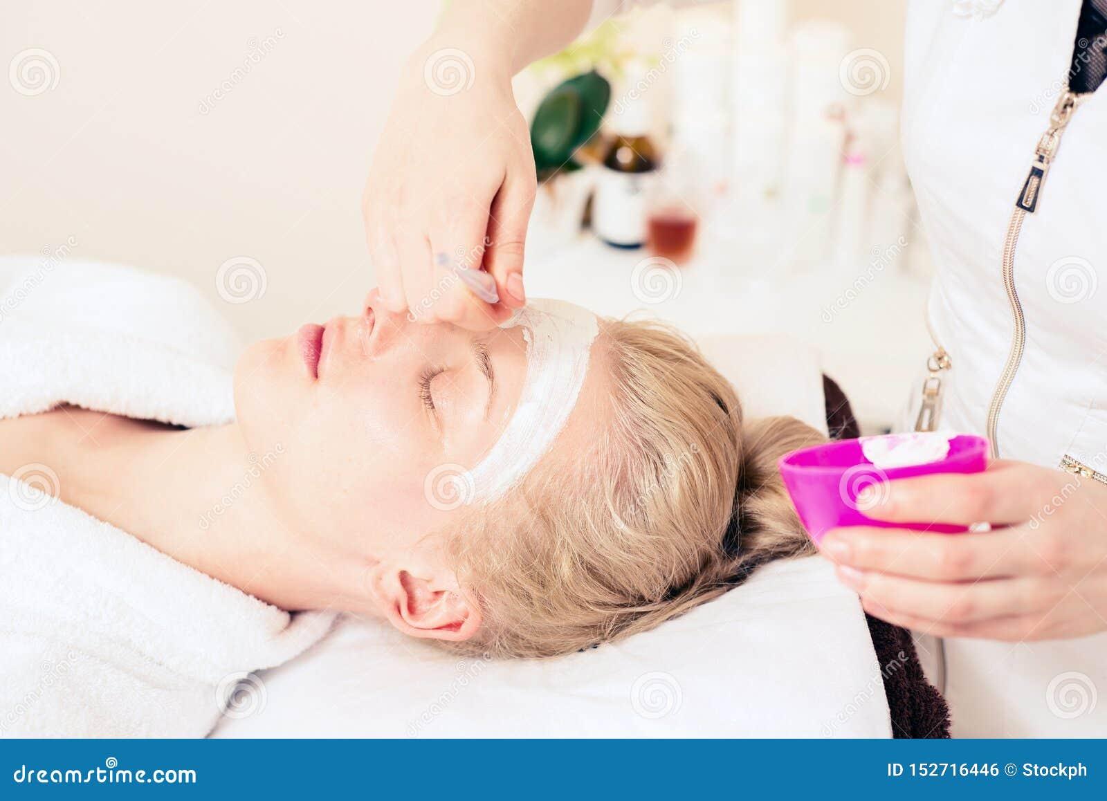 Cosmetologia dos termas o cosmetologist do doutor aplica o creme para enfrentar menina que importa-se com a pele Conceito saud?ve