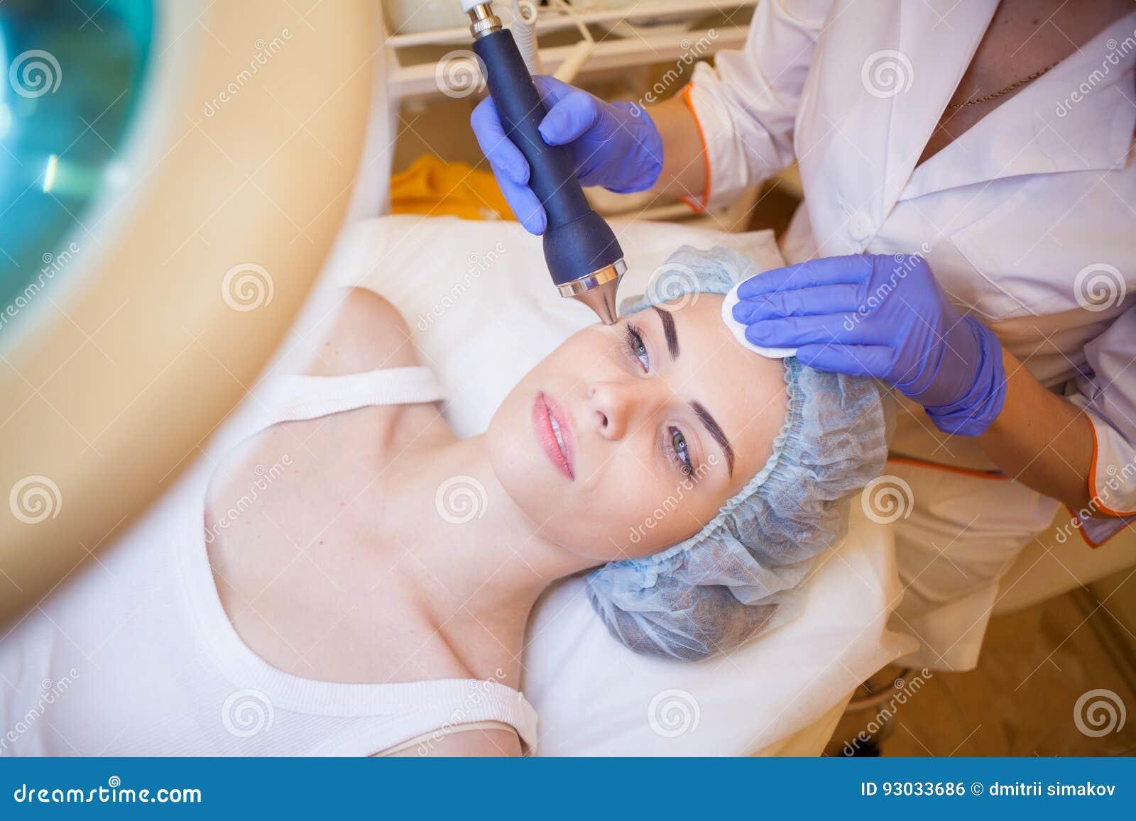 Cosmetologist доктора делая лицевой курорт девушки массажа