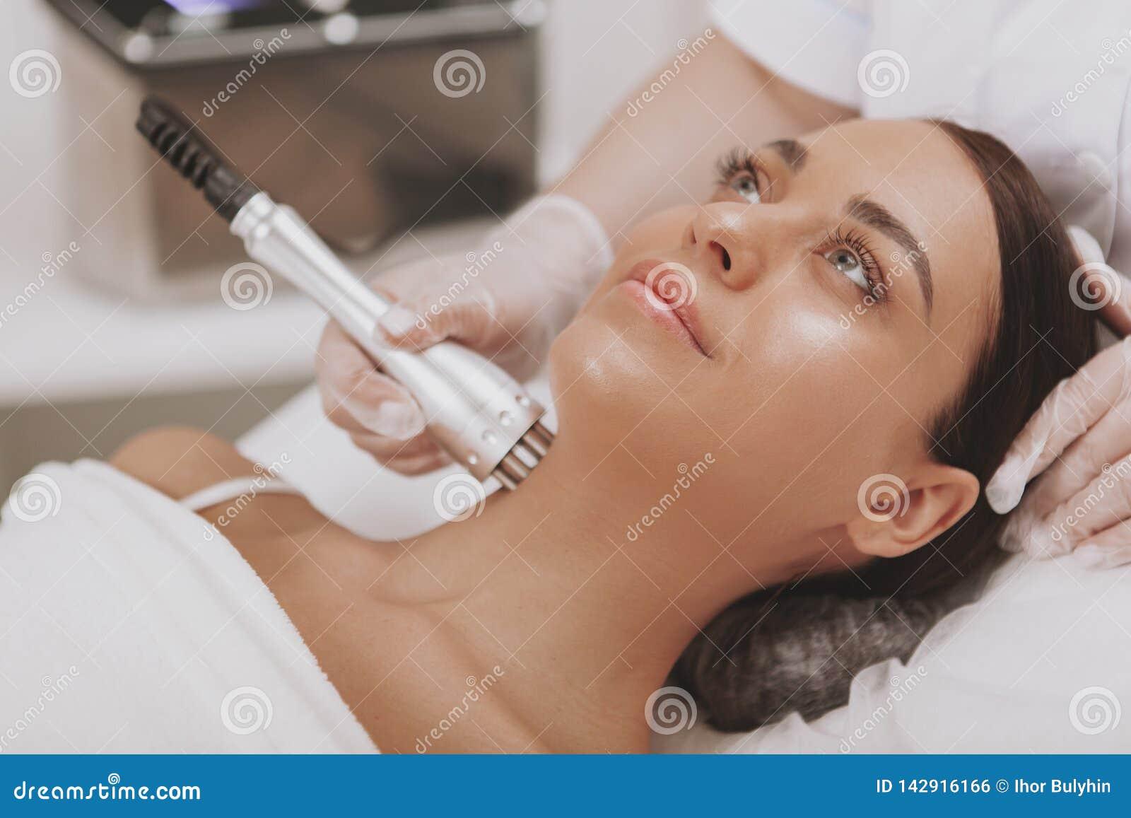 Cosmetologist de visita da jovem mulher bonita na clínica da beleza