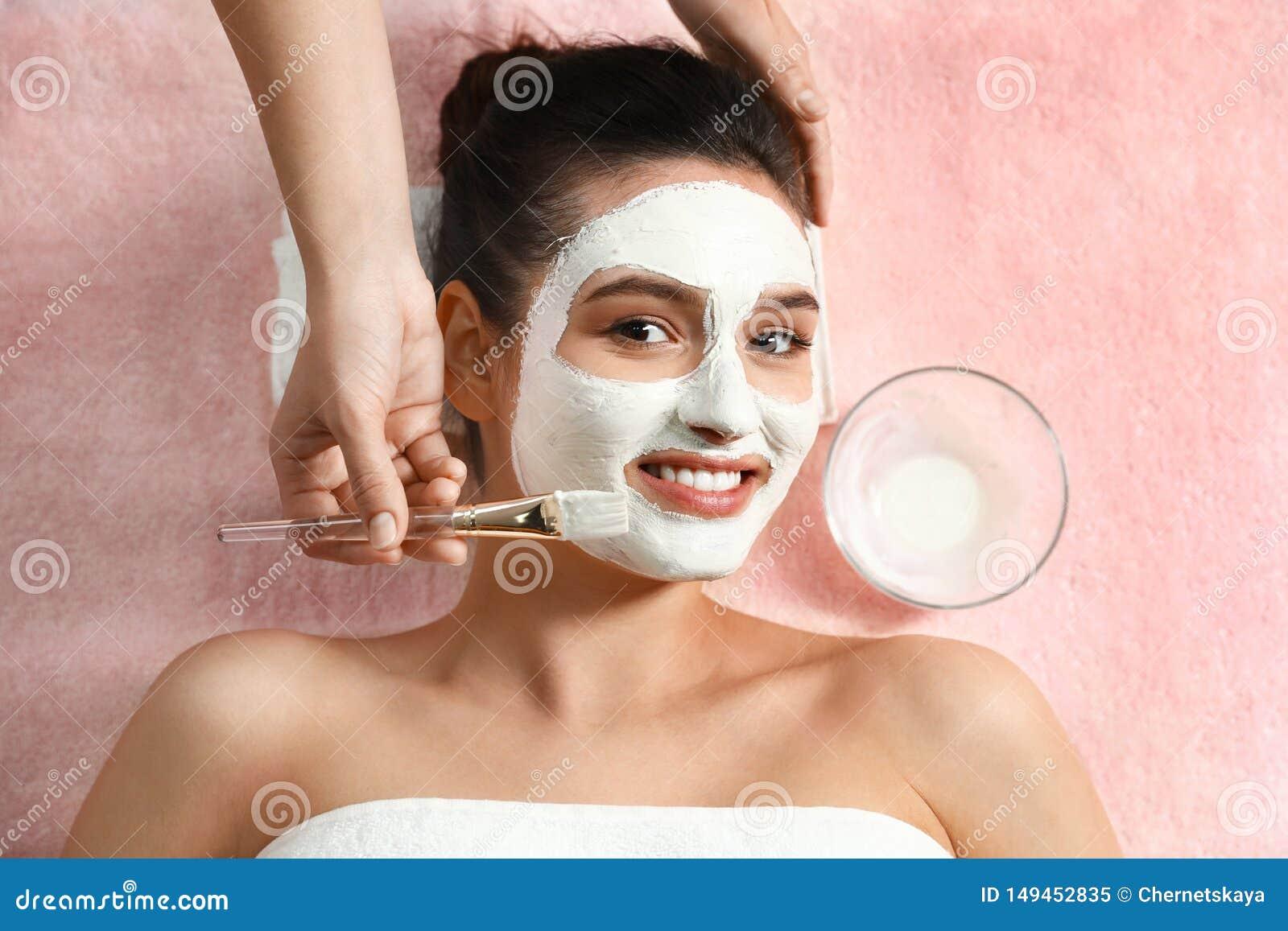 Cosmetologist die wit masker op het gezicht van de vrouw in kuuroordsalon toepassen